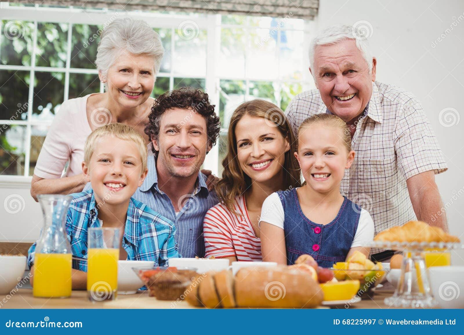 Família feliz da multi-geração pela tabela de café da manhã