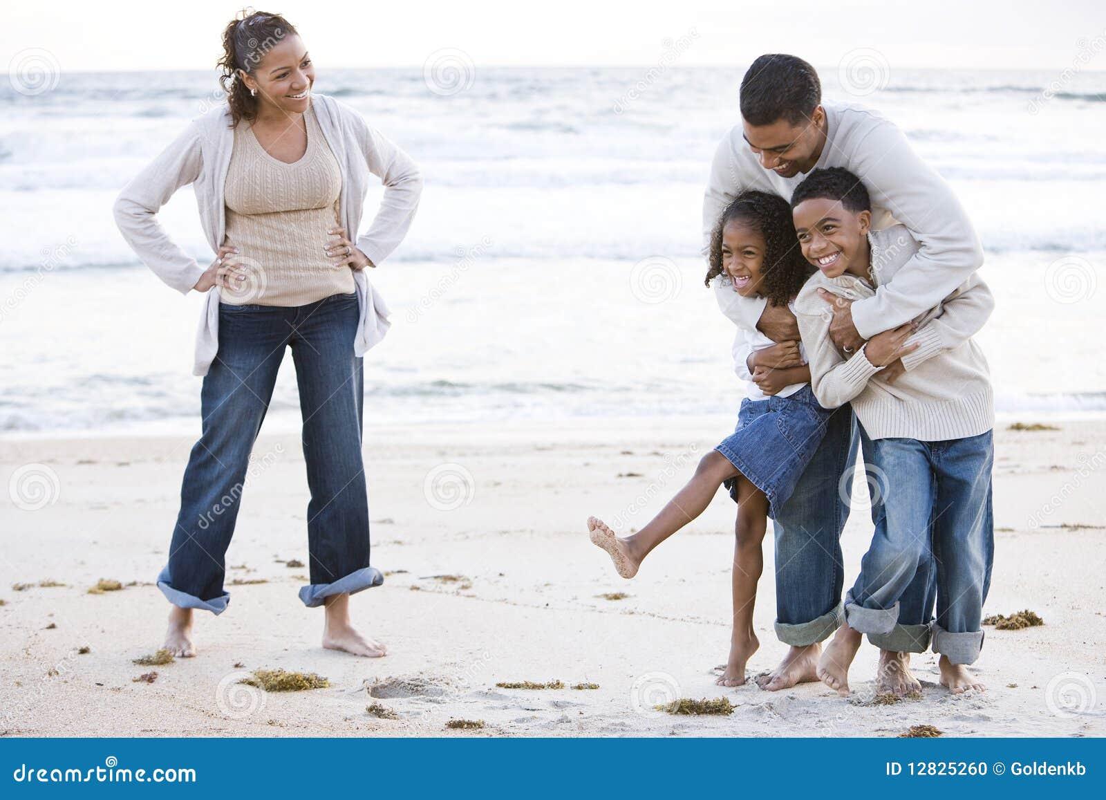 Família feliz do African-American que ri na praia