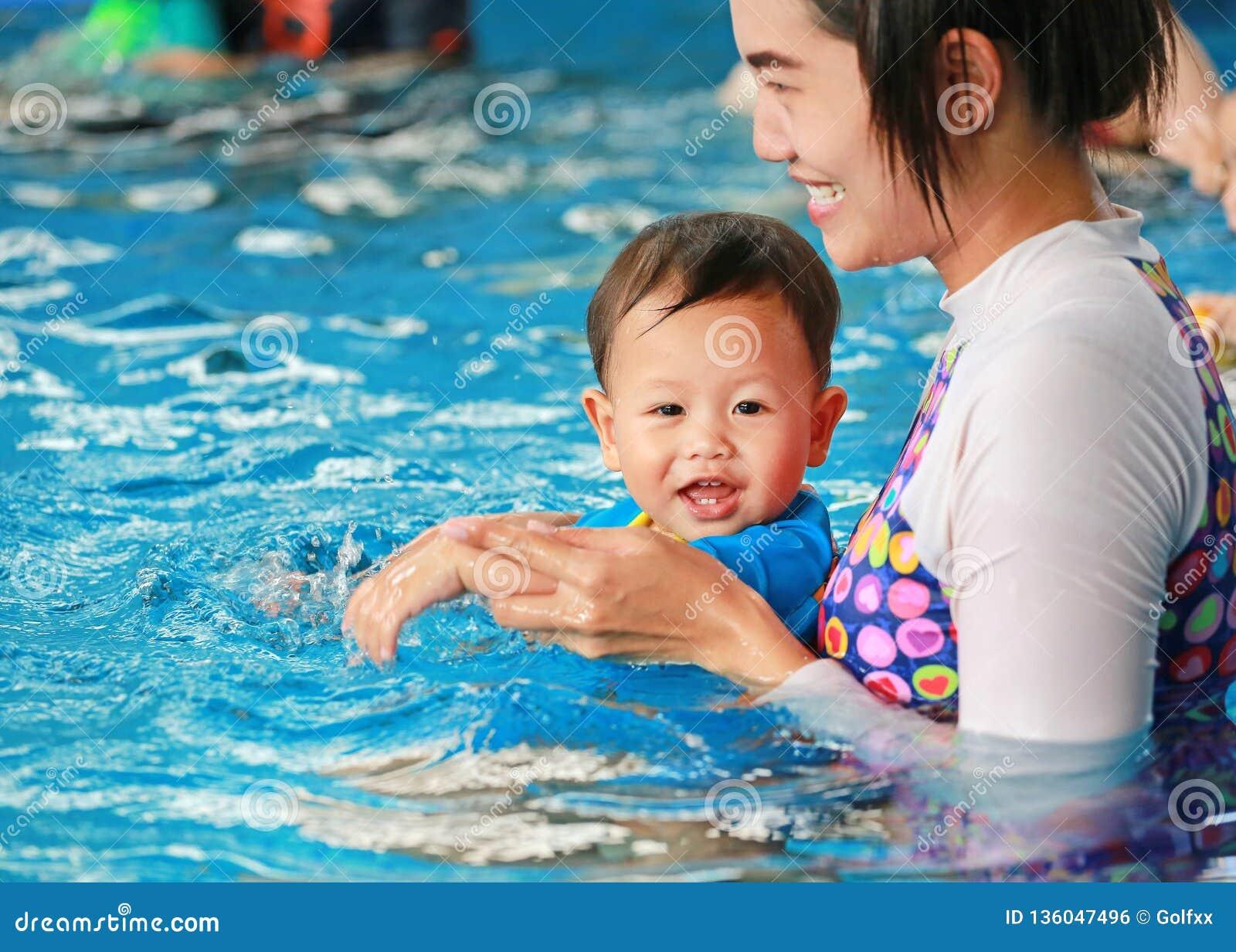 Família feliz do bebê do ensino da mamã na piscina