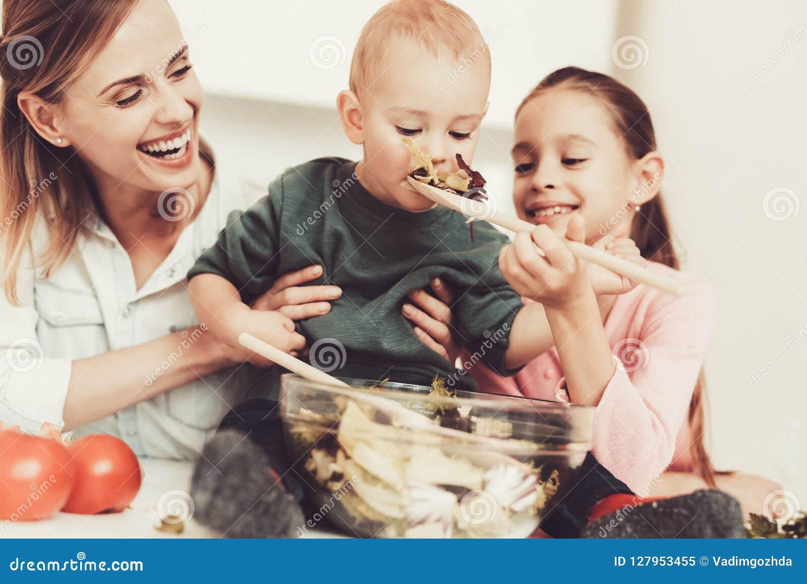 A família feliz está preparando uma salada na cozinha