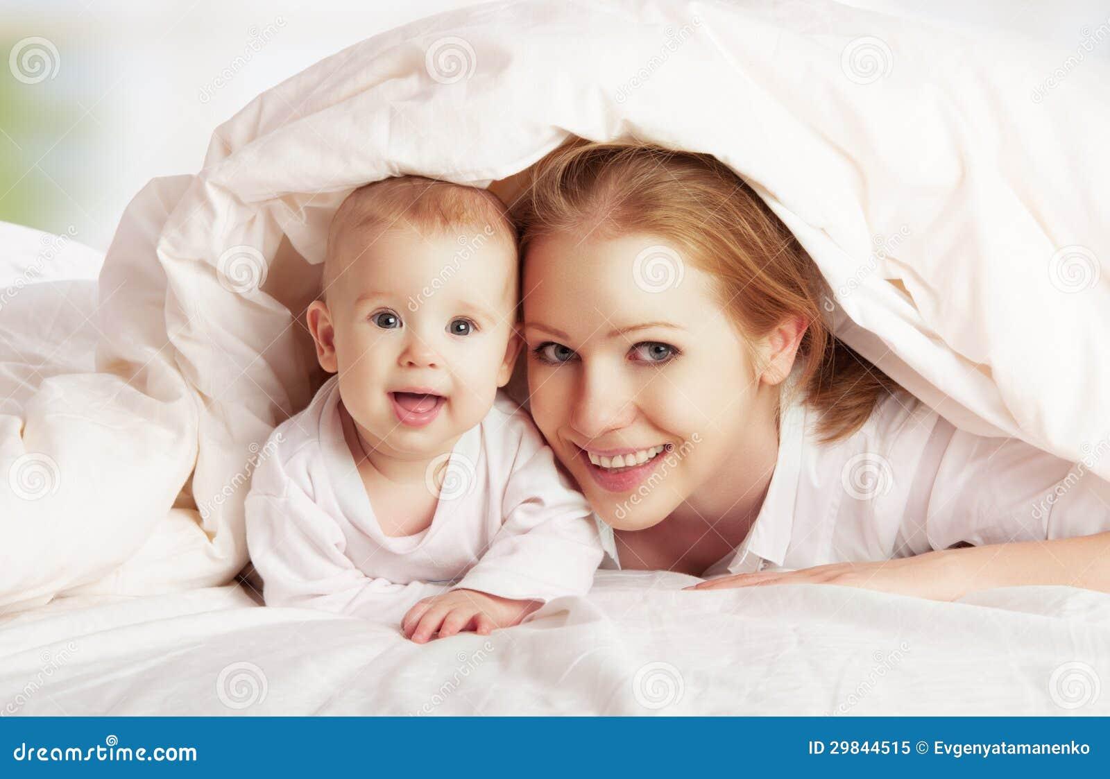 Família feliz. Mãe e bebê que jogam sob a cobertura