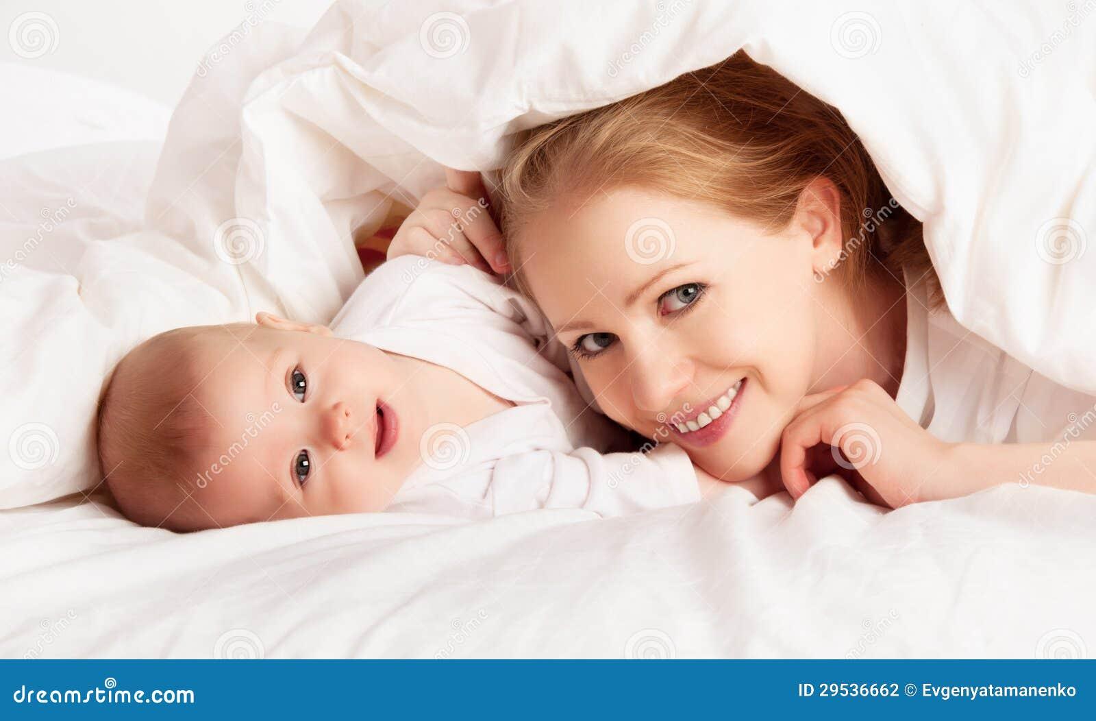 Família feliz. Matriz e bebê que jogam sob a cobertura