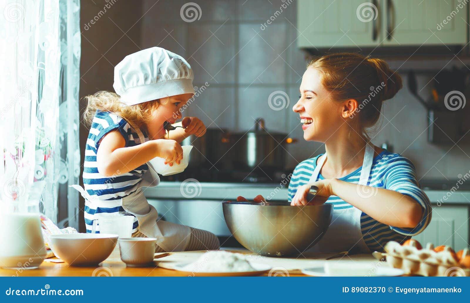 Família feliz na cozinha a mãe e a criança que preparam a massa, cozem