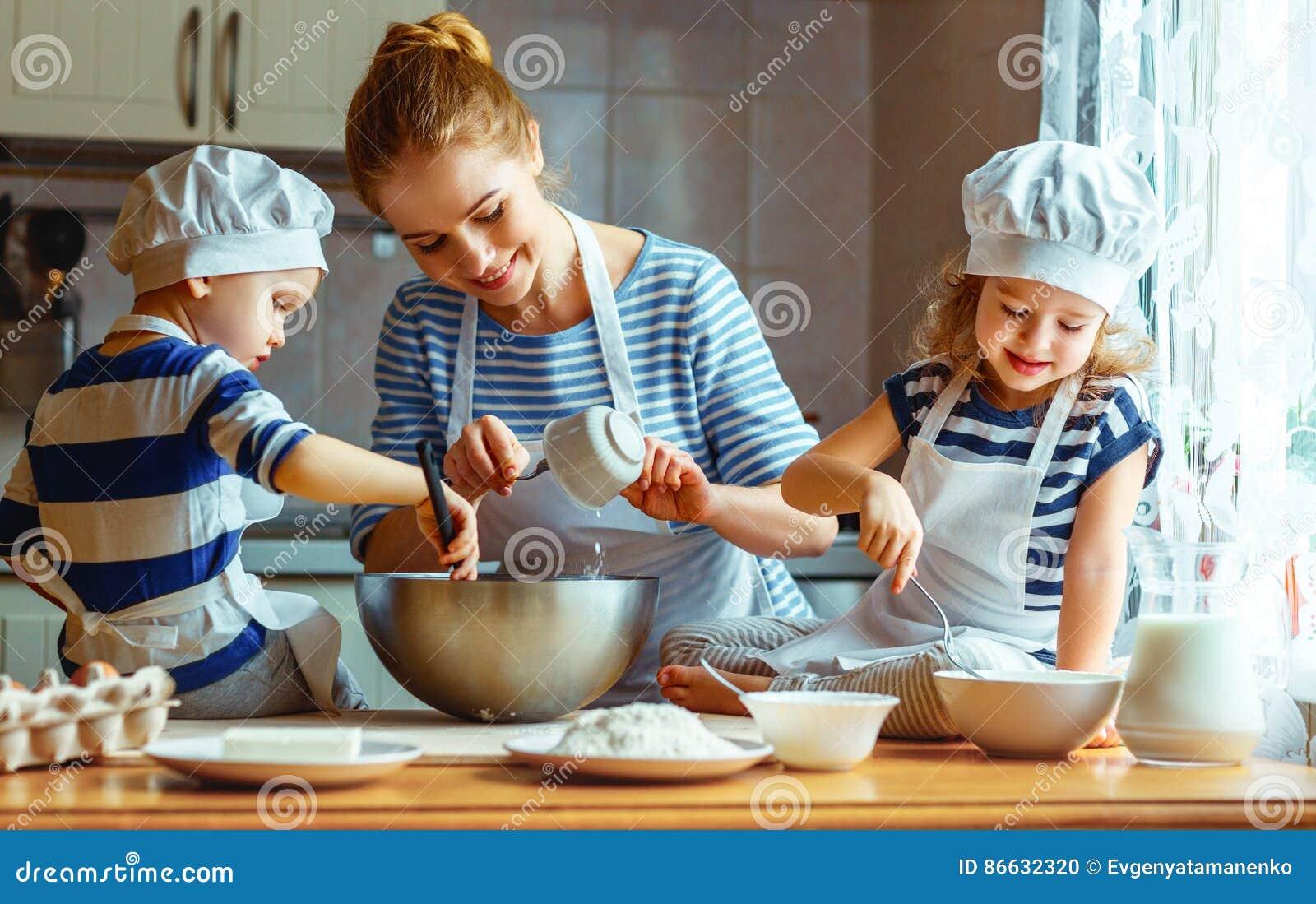 Família feliz na cozinha mãe e crianças que preparam a massa, vagabundos
