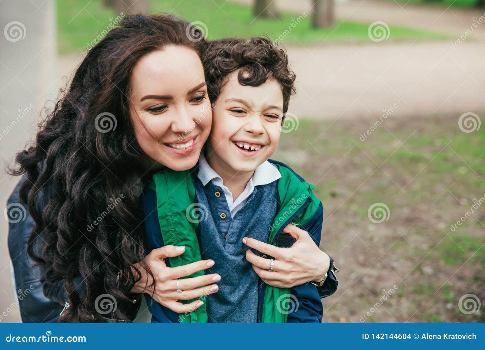 Família feliz no parque da mola mãe nova e seu filho que passam o tempo exterior em um dia de verão
