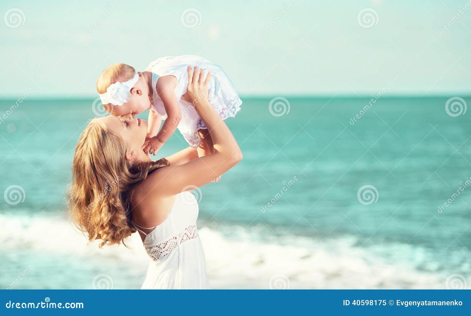 Família feliz no vestido branco A mãe joga acima o bebê no céu