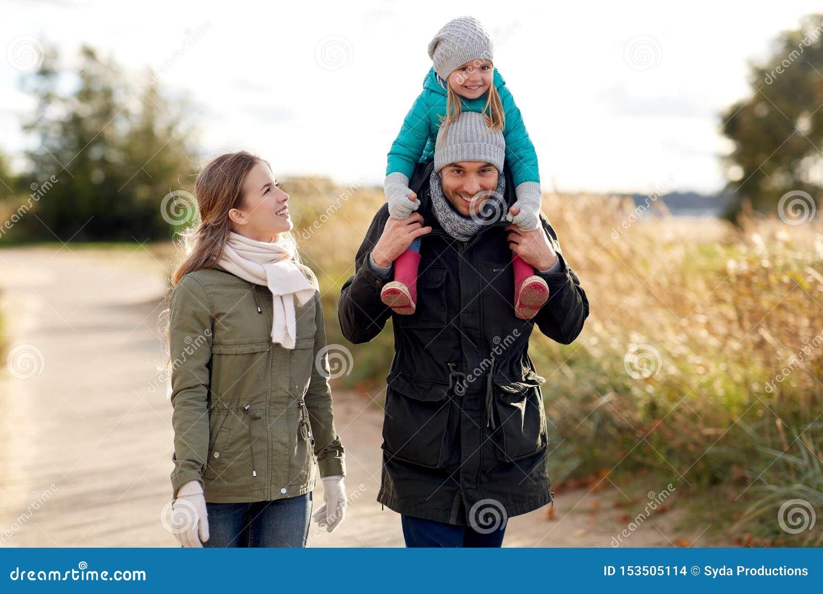 Família feliz que anda no outono