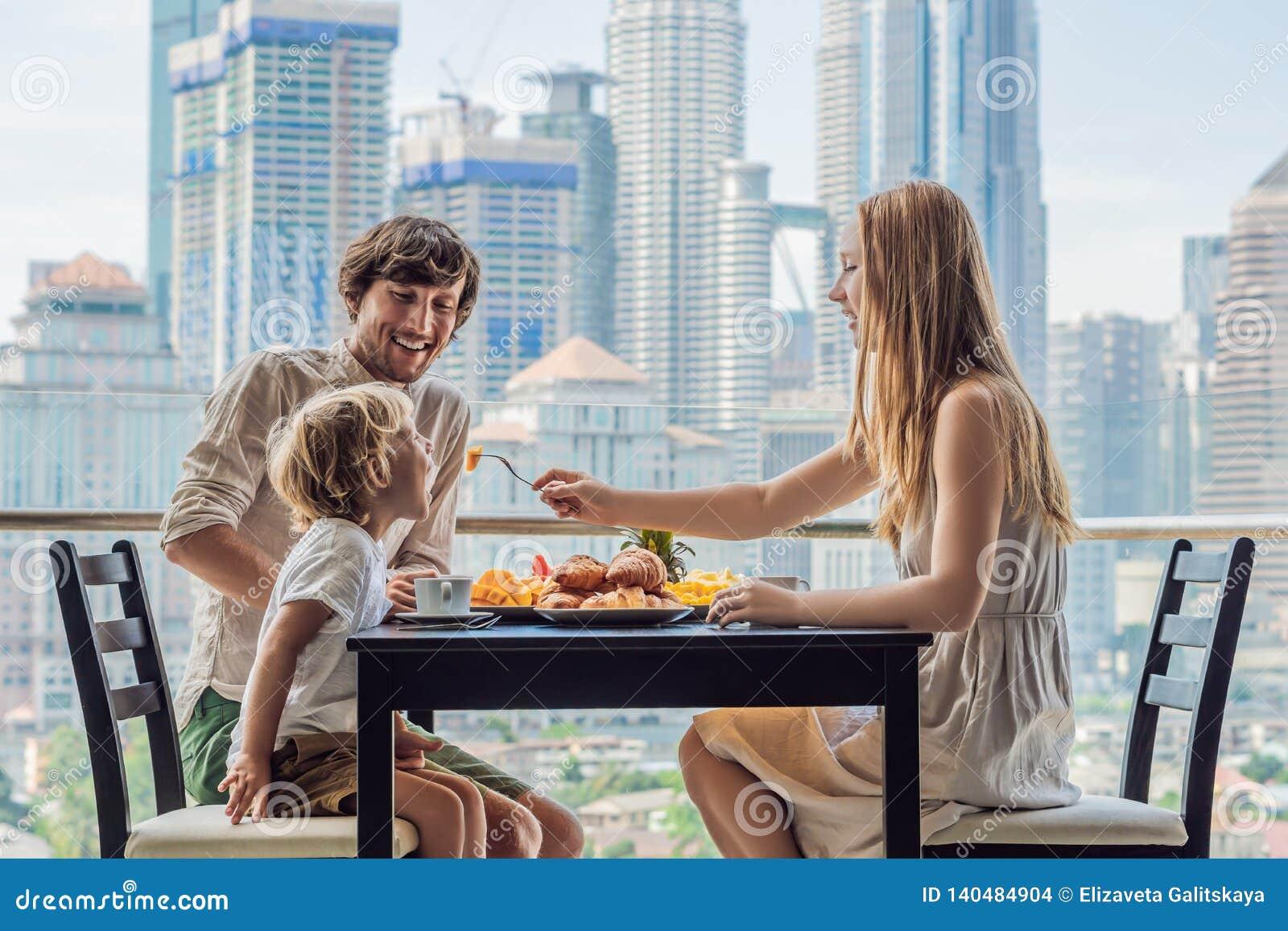 Família feliz que come o café da manhã no balcão Tabela de café da manhã com o fruto e o pão do café croisant em um balcão contra