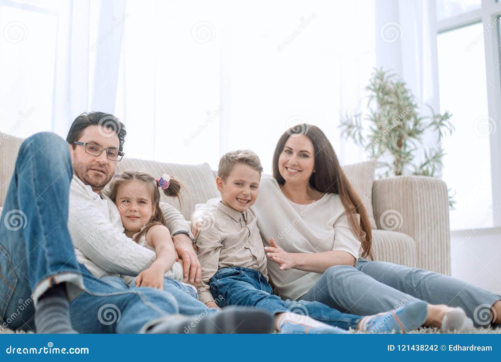 Família feliz que descansa em sua sala de visitas confortável