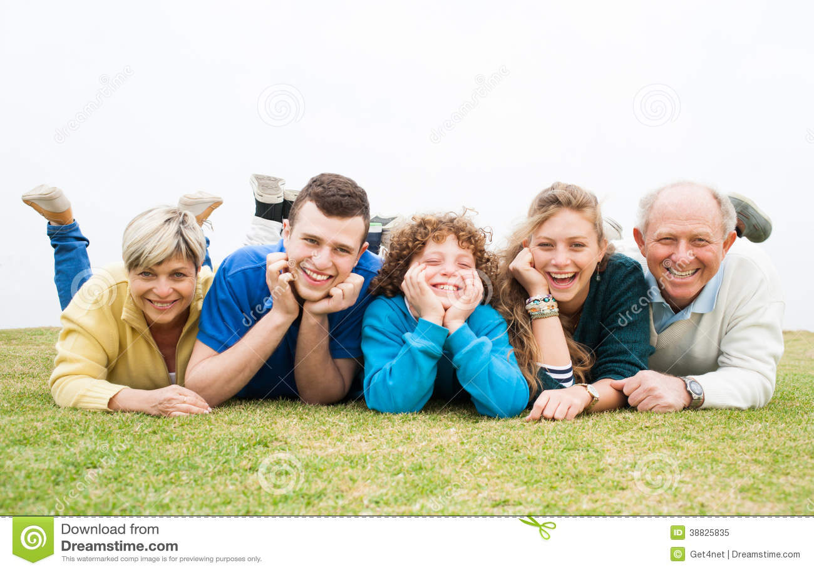 Família feliz que encontra-se no gramado verde