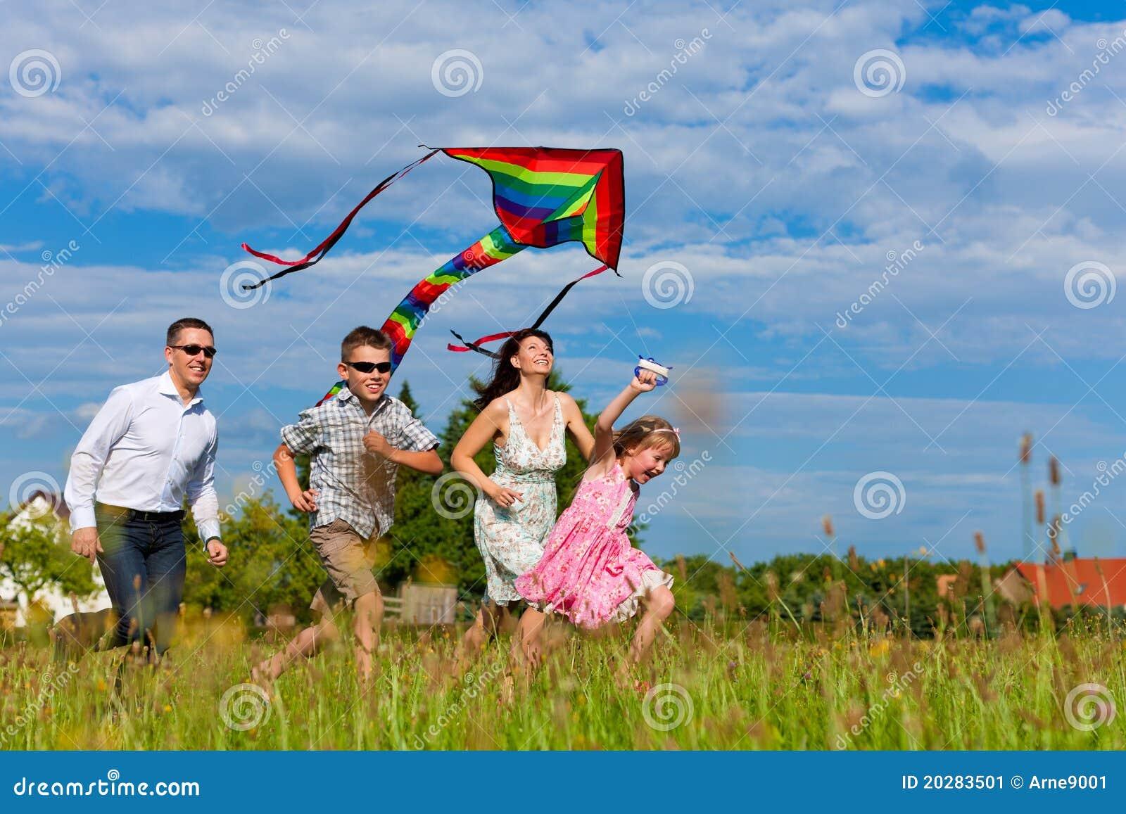 Família feliz que funciona no prado com um papagaio