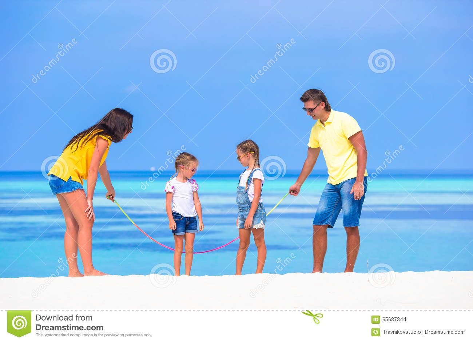 Família feliz que joga na praia tropical branca