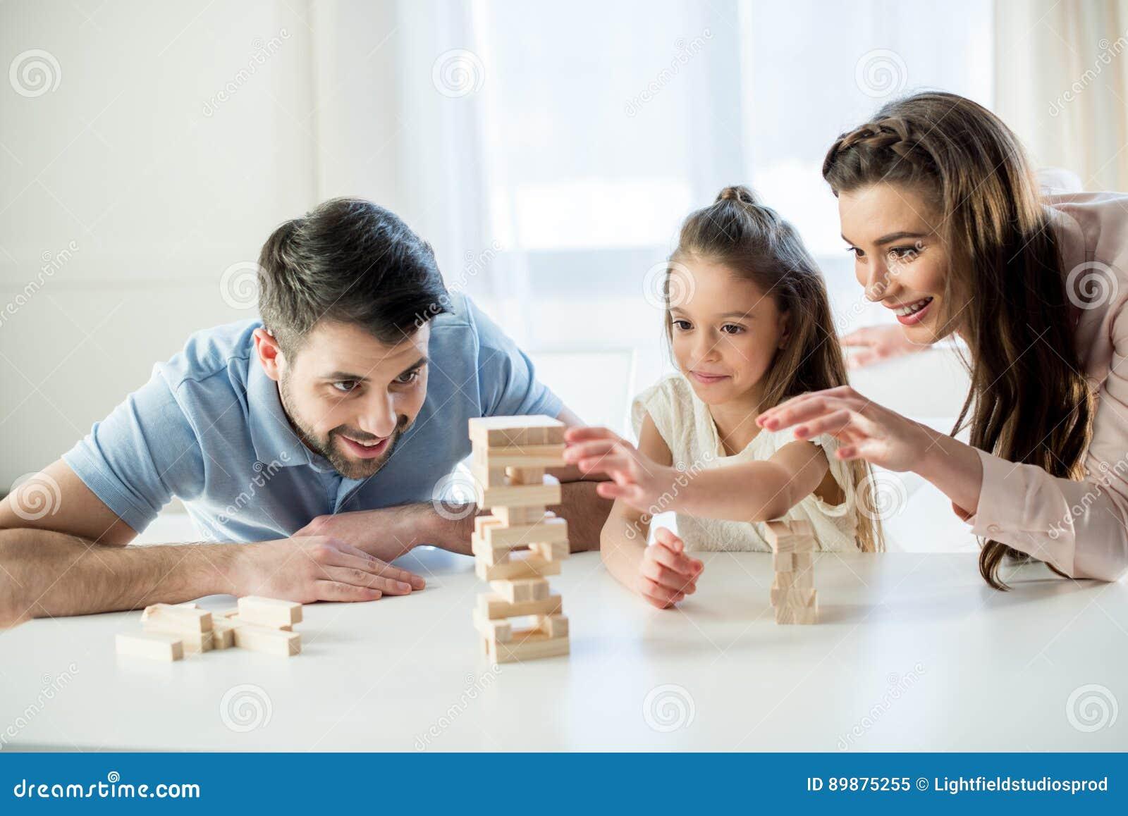 Família feliz que joga o jogo do jenga em casa