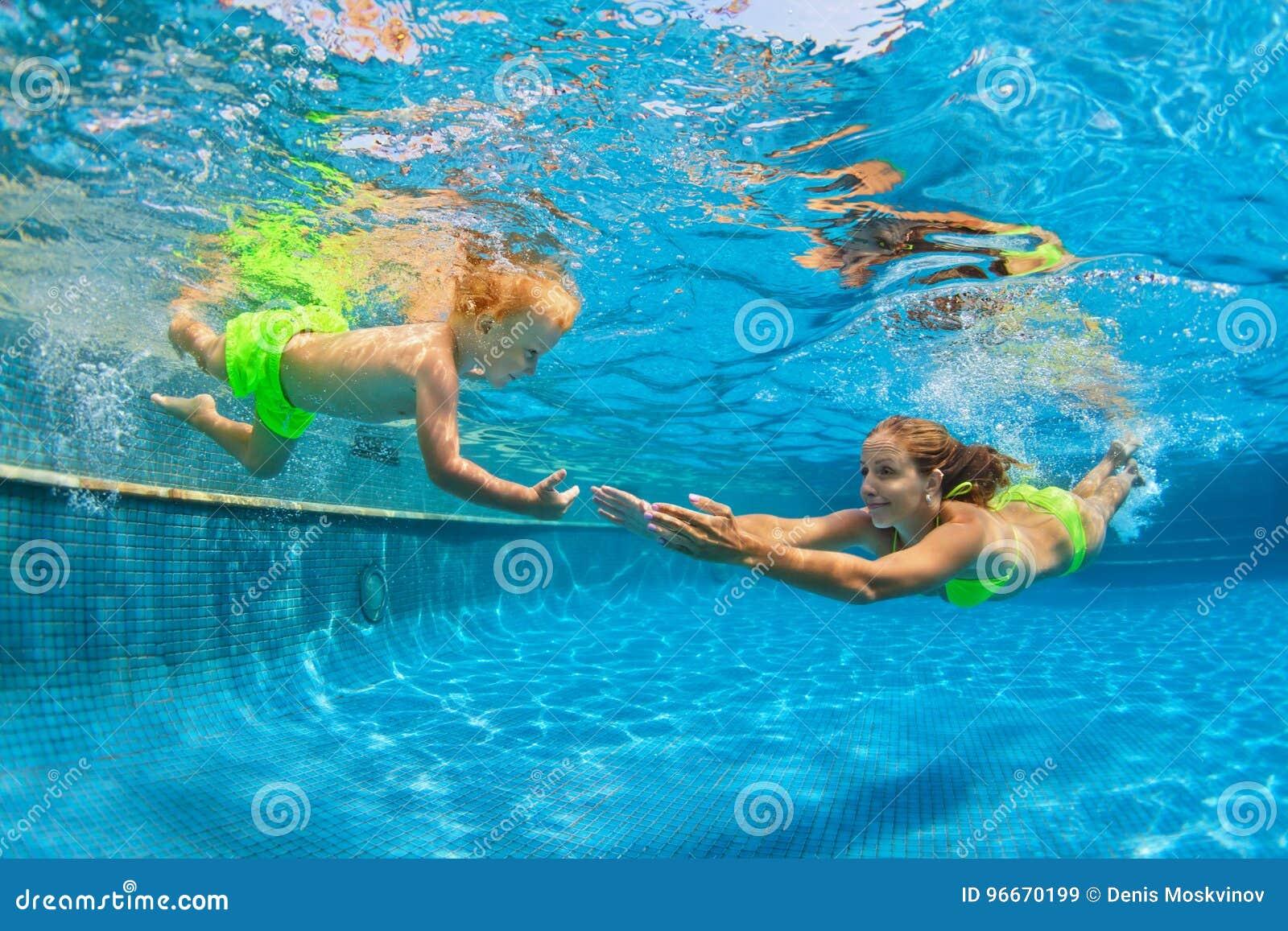 Família feliz que mergulha debaixo d água com divertimento na piscina