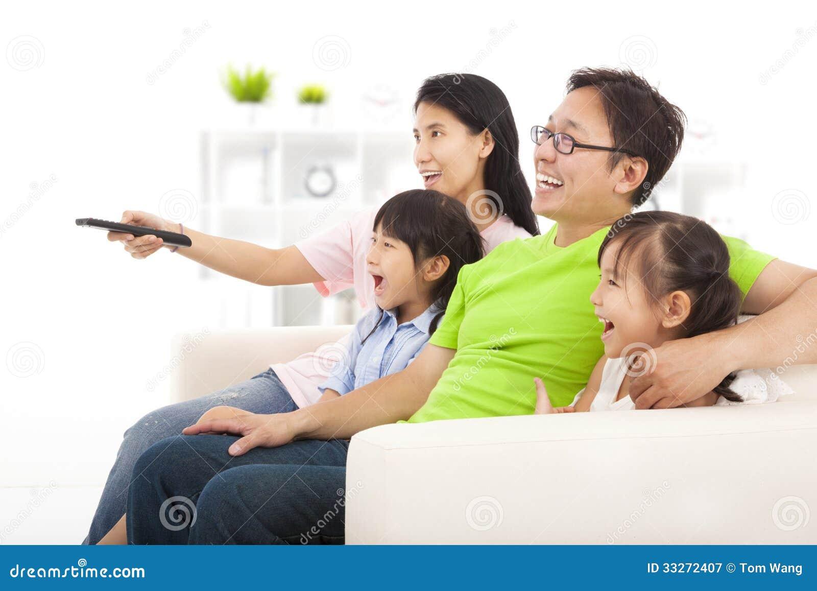 Família feliz que olha a tevê