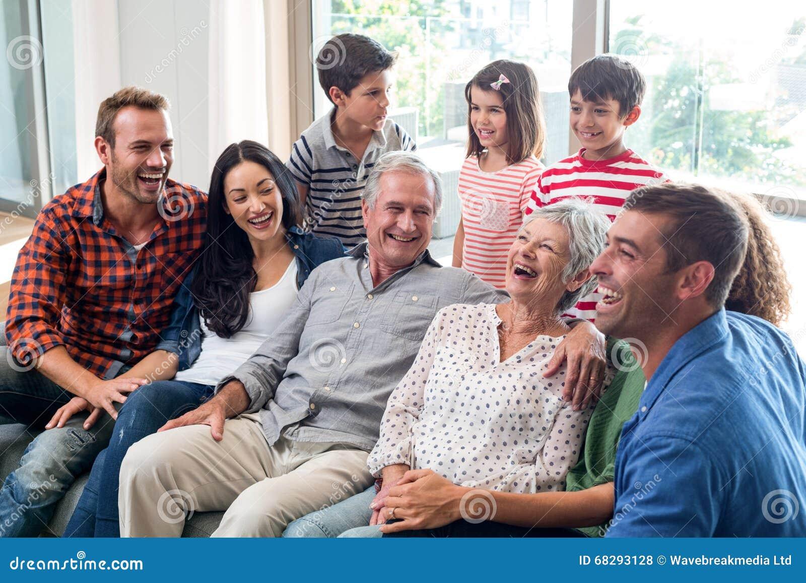 Família feliz que senta-se no sofá