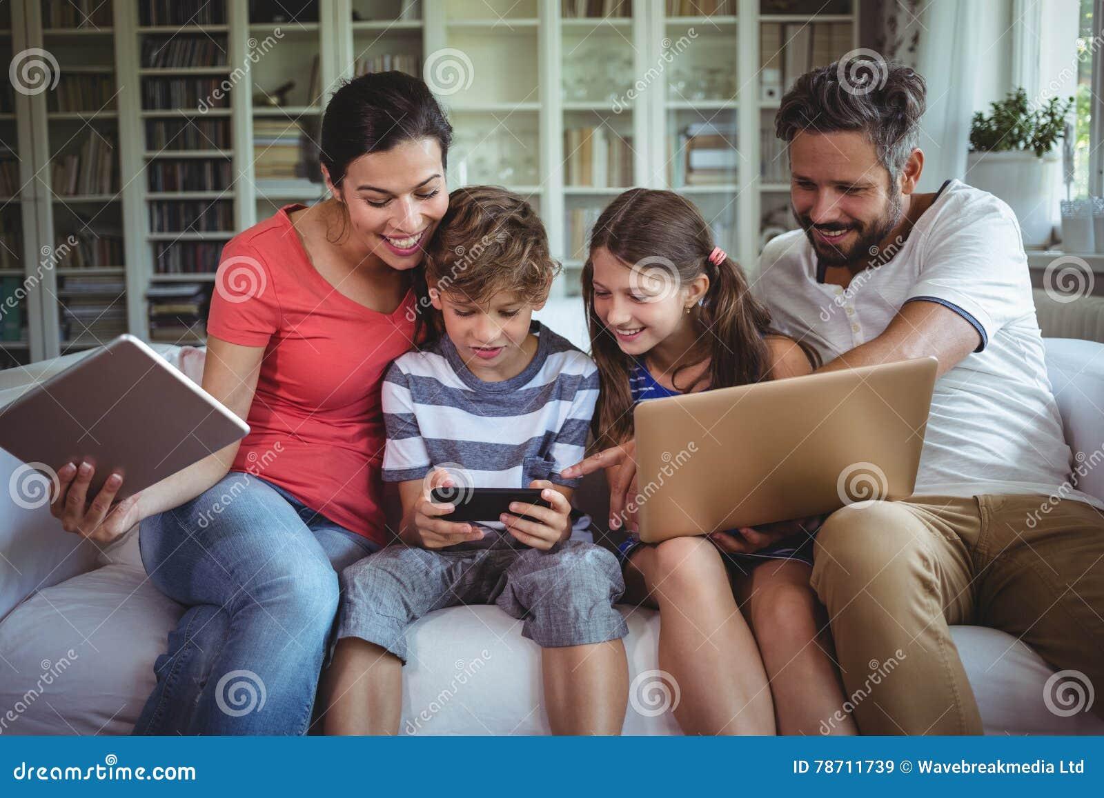 Família feliz que senta-se no sofá e que usa o portátil, o telefone celular e a tabuleta digital