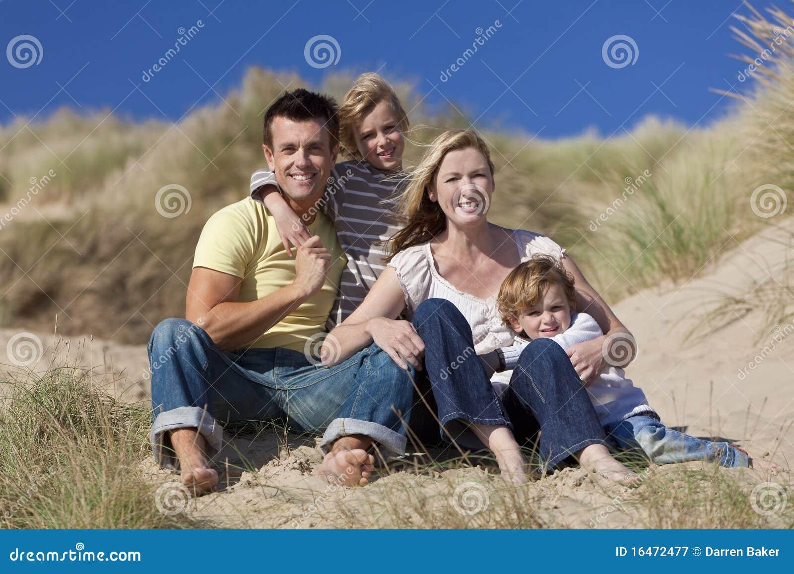 Família feliz que senta-se tendo o divertimento na praia