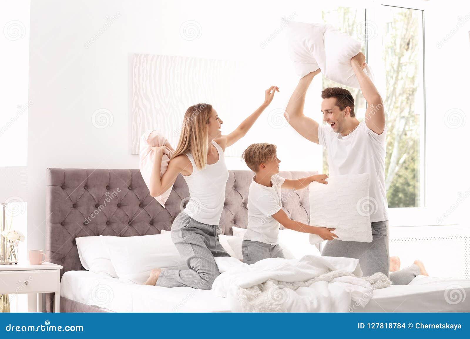 Família feliz que tem a luta de descanso na cama