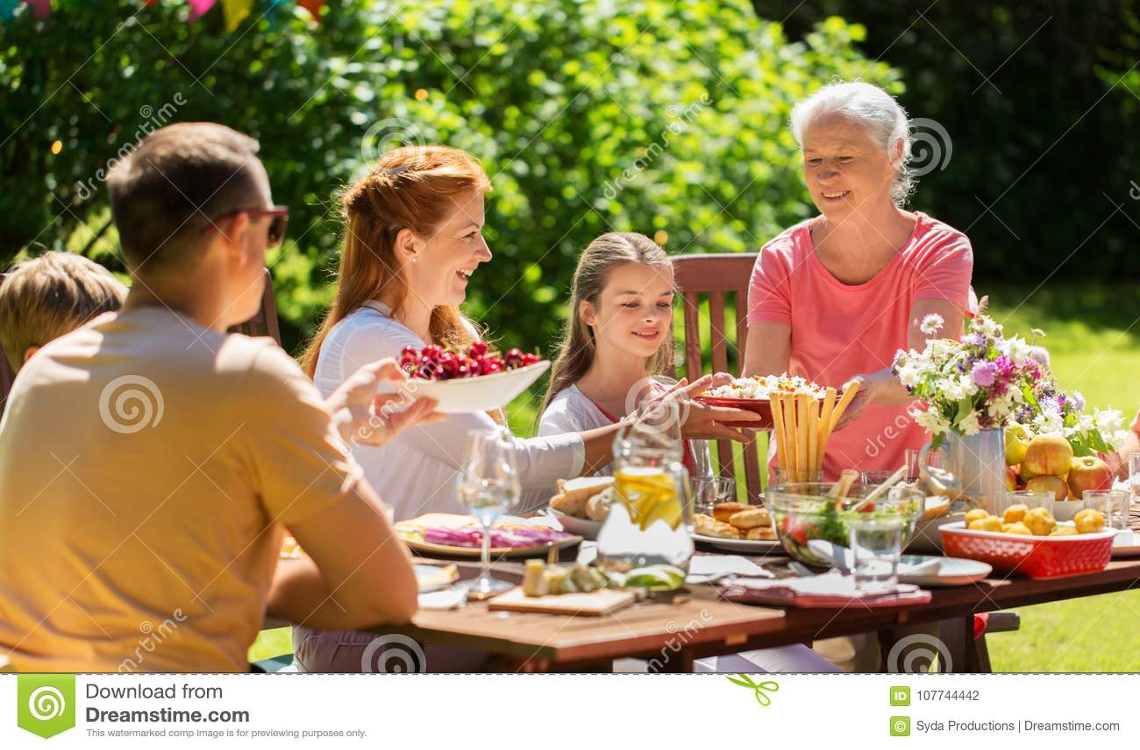 Família feliz que tem o jantar ou o partido de jardim do verão