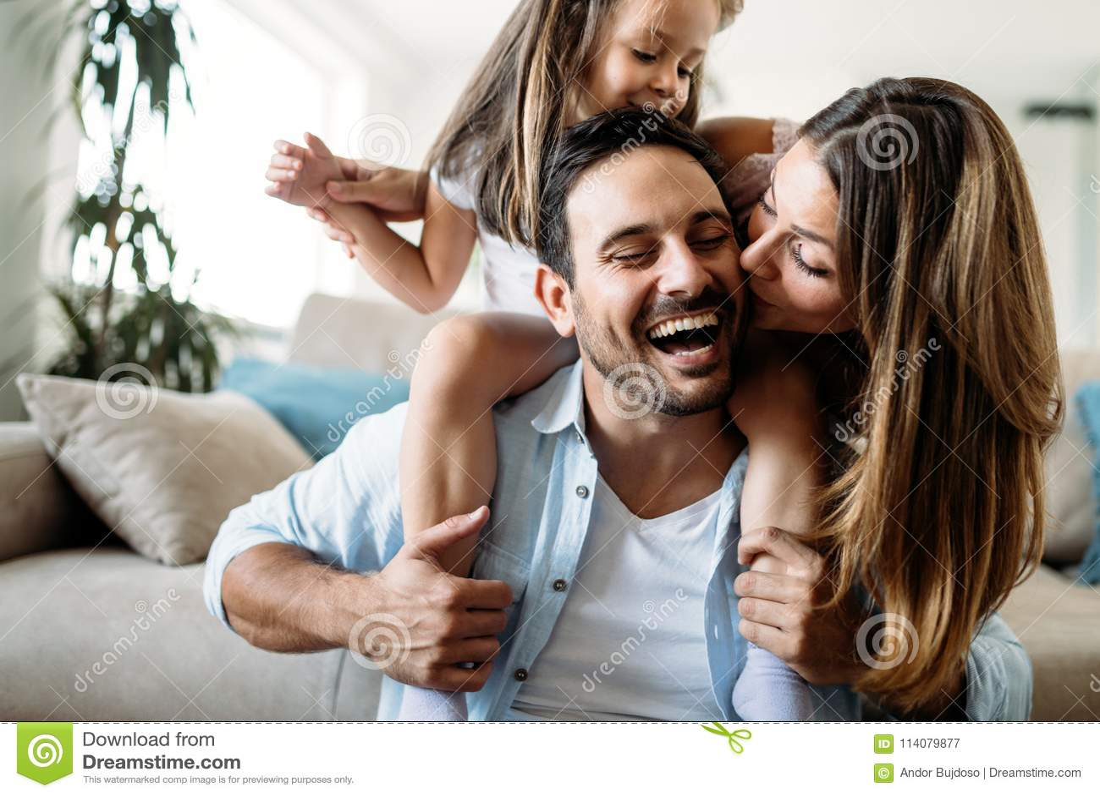 Família feliz que tem o tempo do divertimento em casa