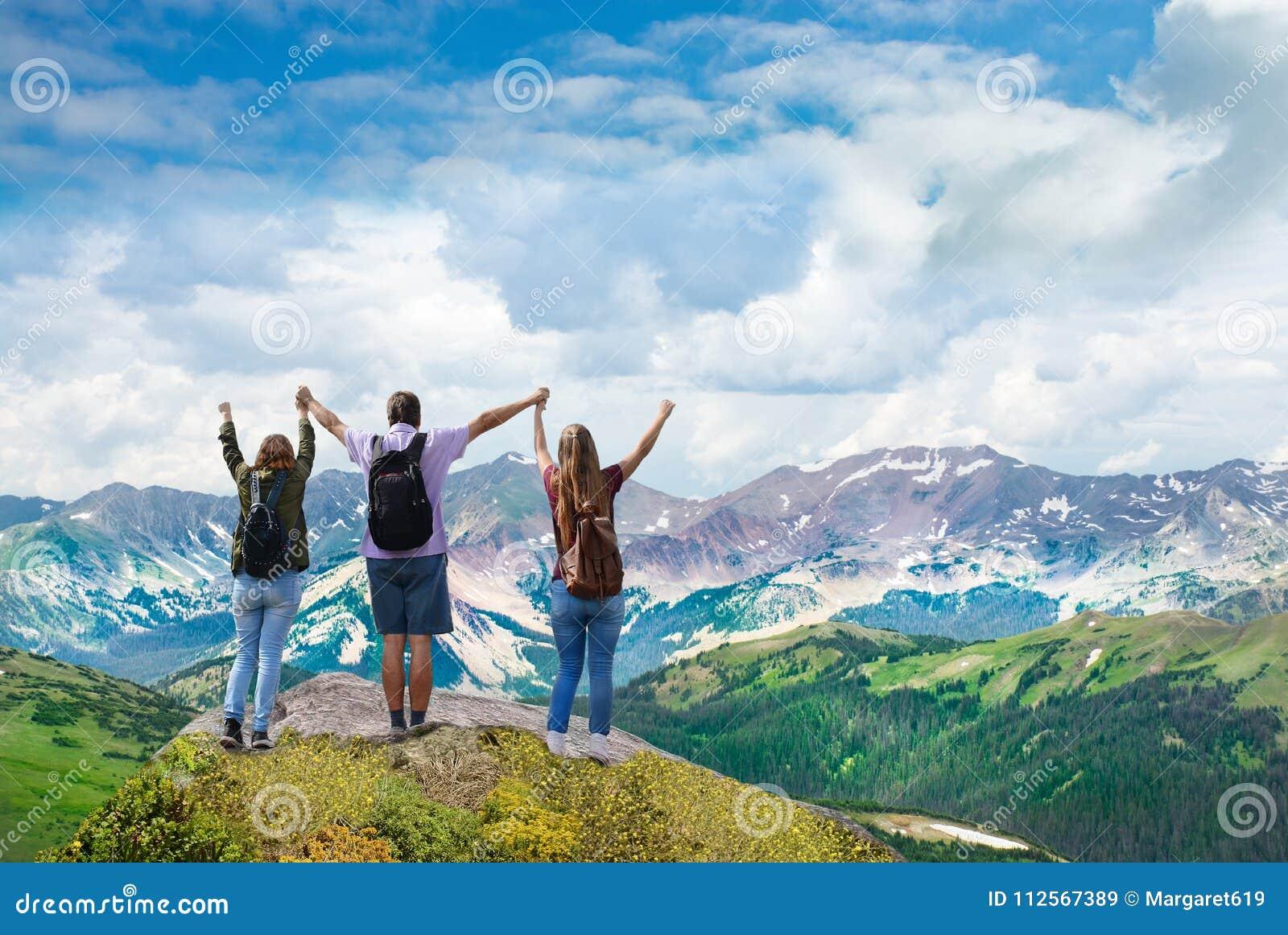 A família feliz sobre a terra arrendada bonita da montanha levantou as mãos