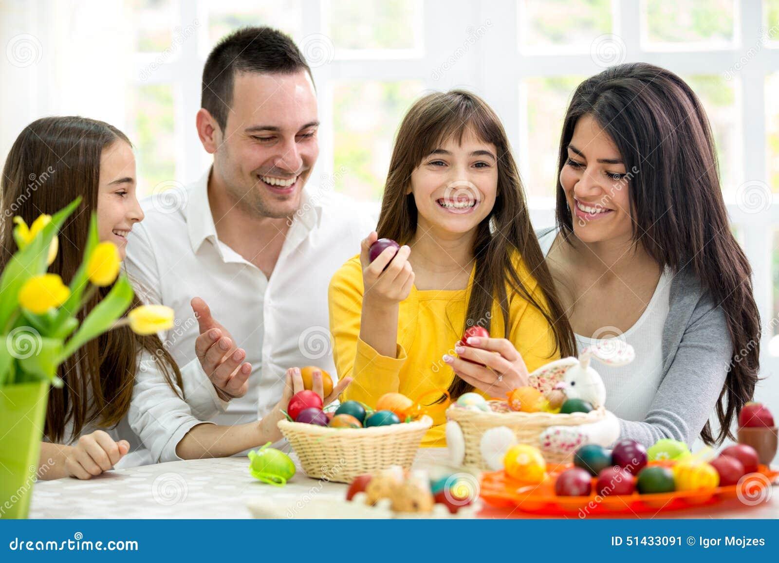 A família feliz tem o divertimento com ovos da páscoa