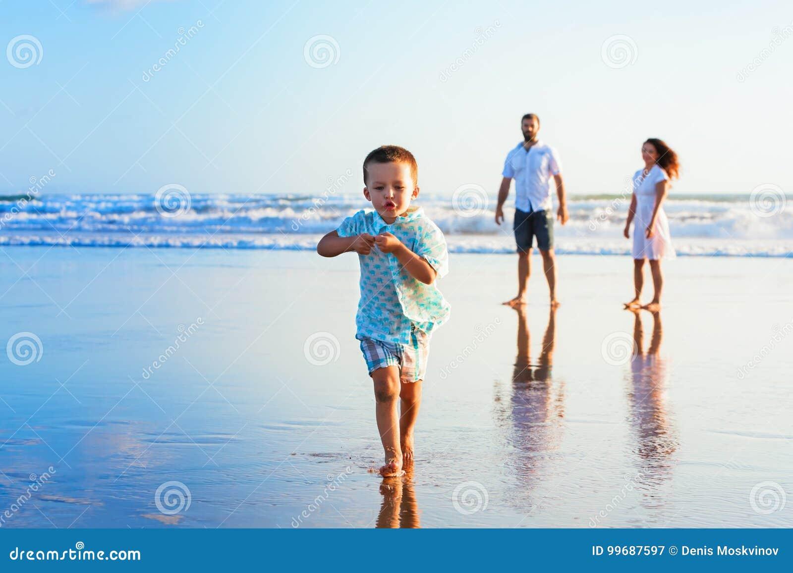 A família feliz tem o divertimento na praia do por do sol