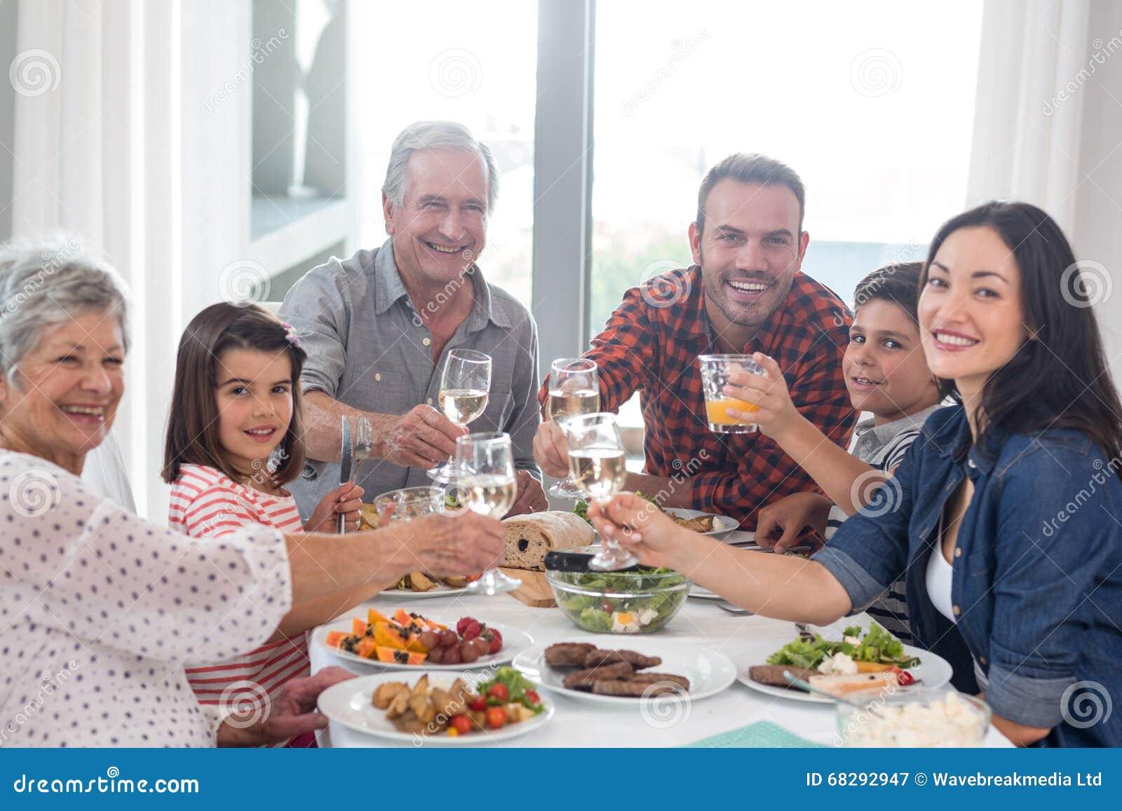 Família junto que tem a refeição