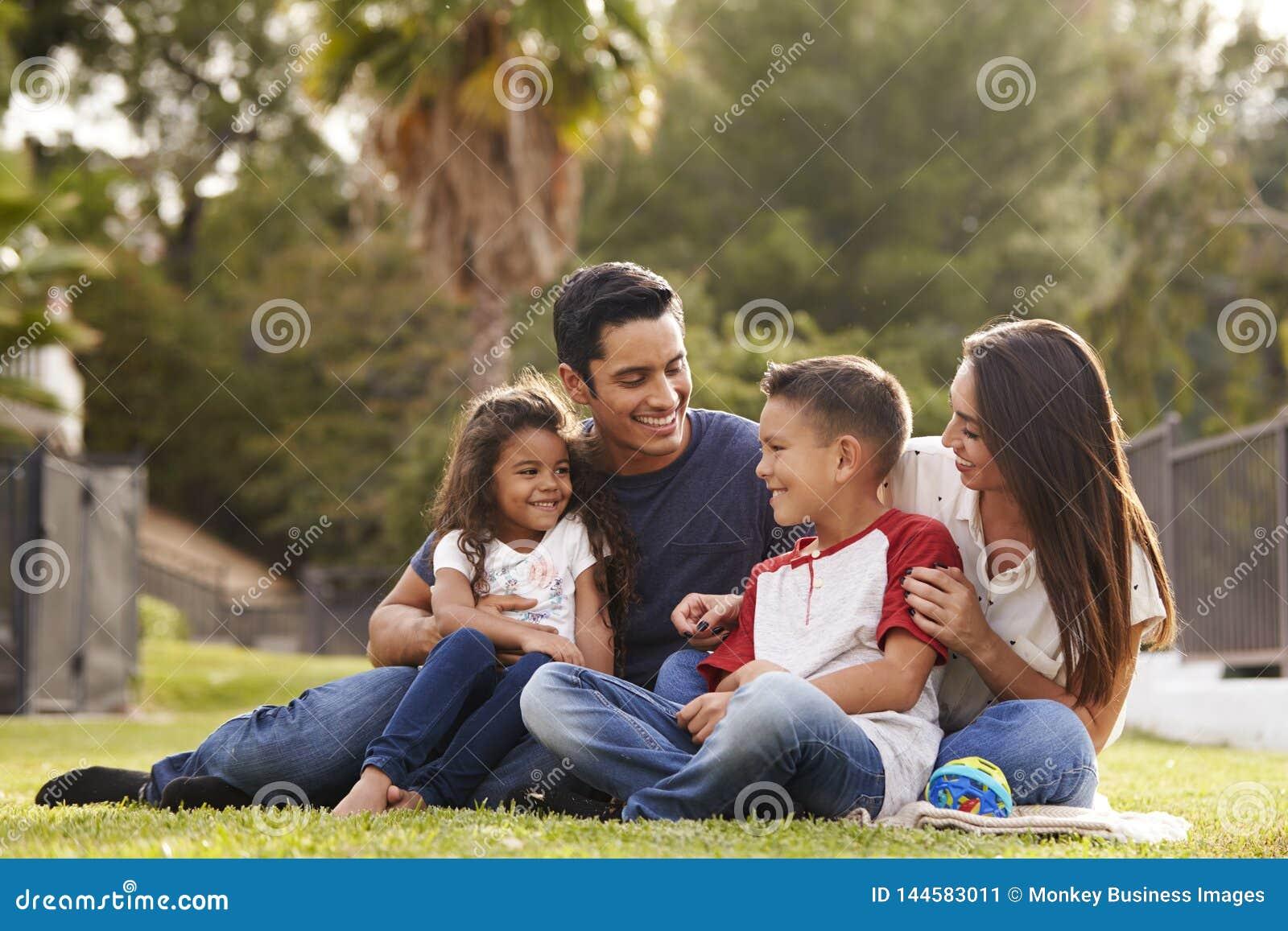 Família latino-americano nova feliz que senta-se junto na grama no parque, olhando se