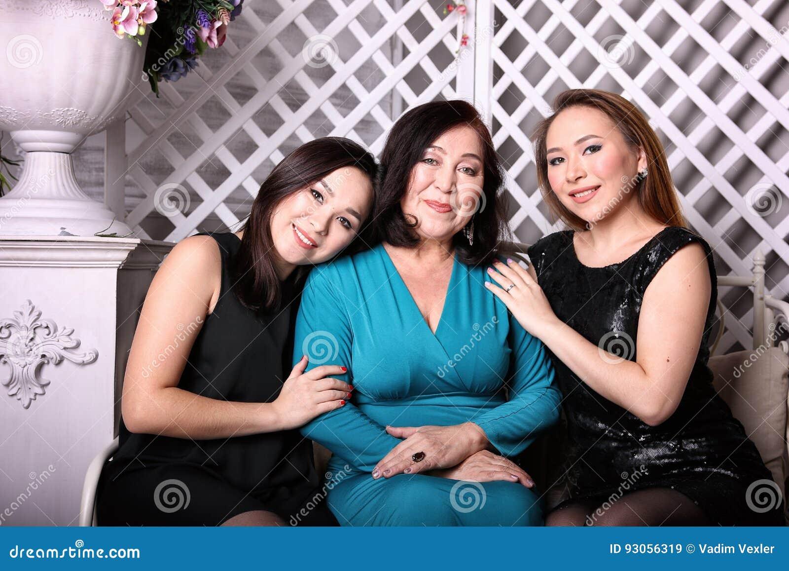 A família, a mamã e a filha asiáticas em vestidos de noite sentam-se no sofá