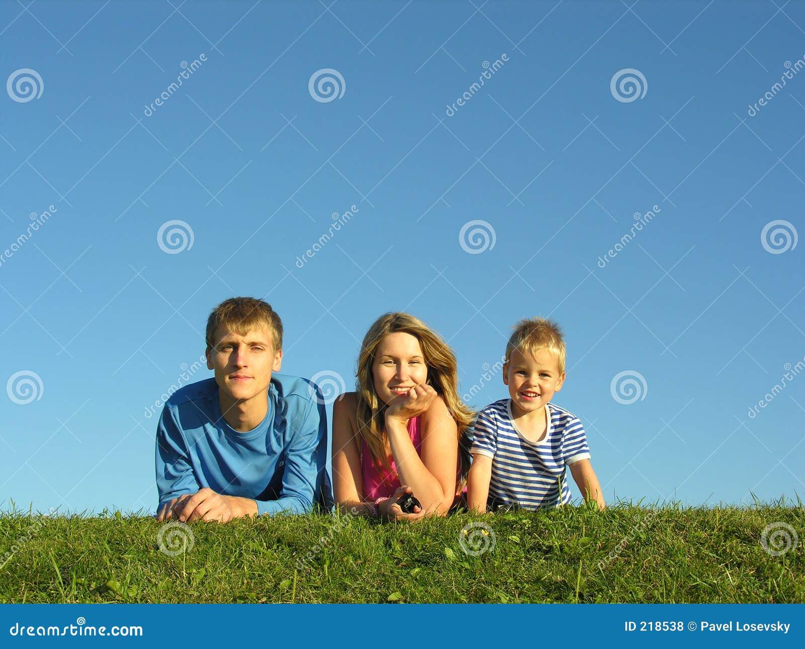 Família na erva sob o céu azul