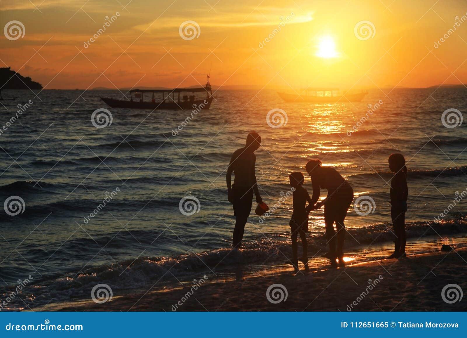 Família na praia no por do sol