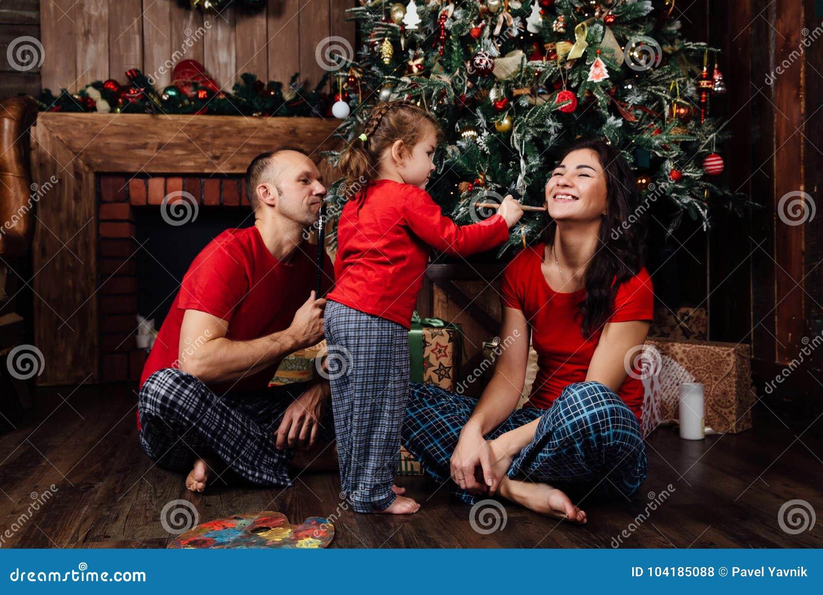fc003de89549bb A Família Nos Pijamas Joga Ao Lado De Uma árvore De Natal E De Uma ...