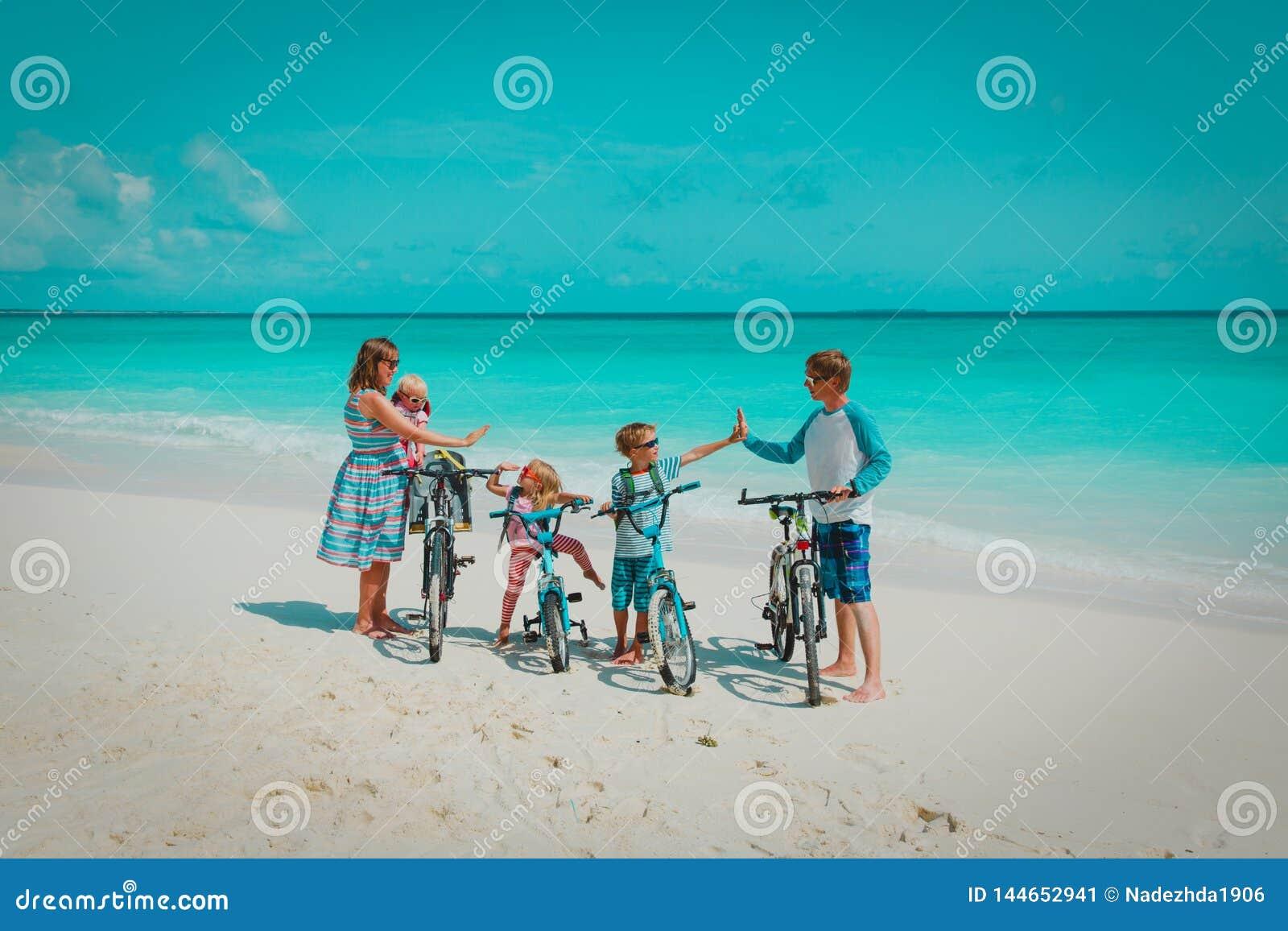 Família nova feliz com as crianças que montam bicicletas na praia
