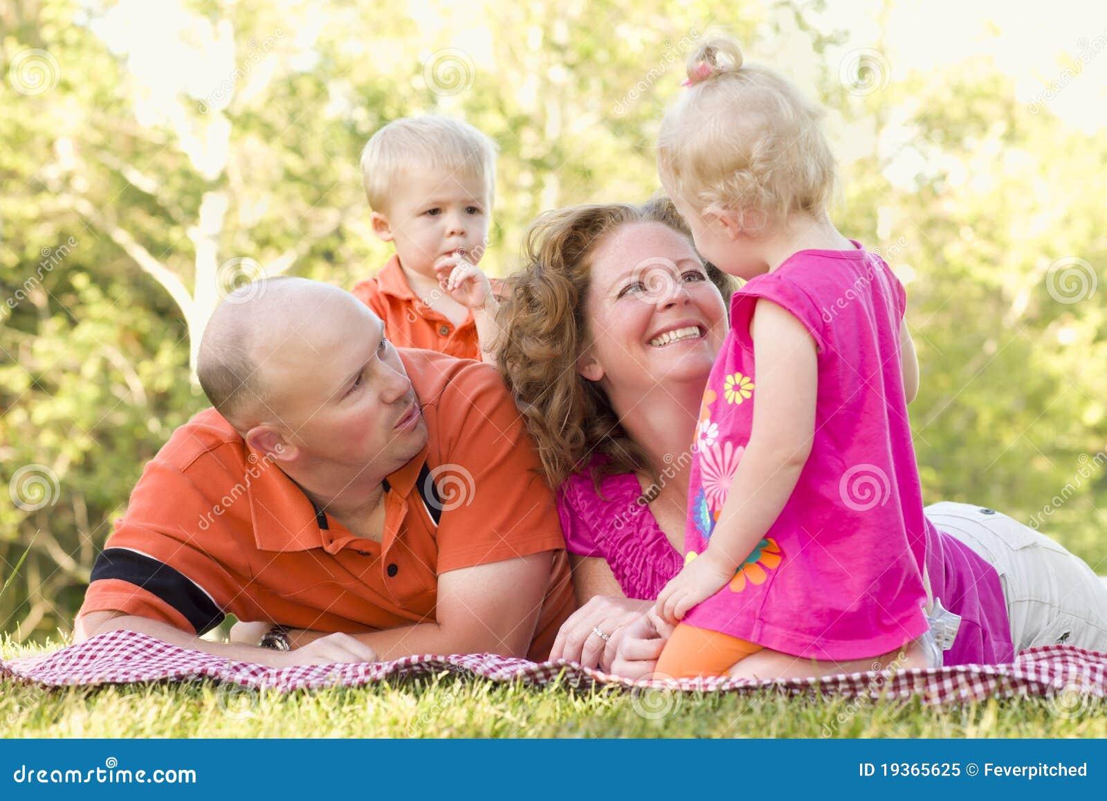 Família nova feliz com os gêmeos bonitos no parque