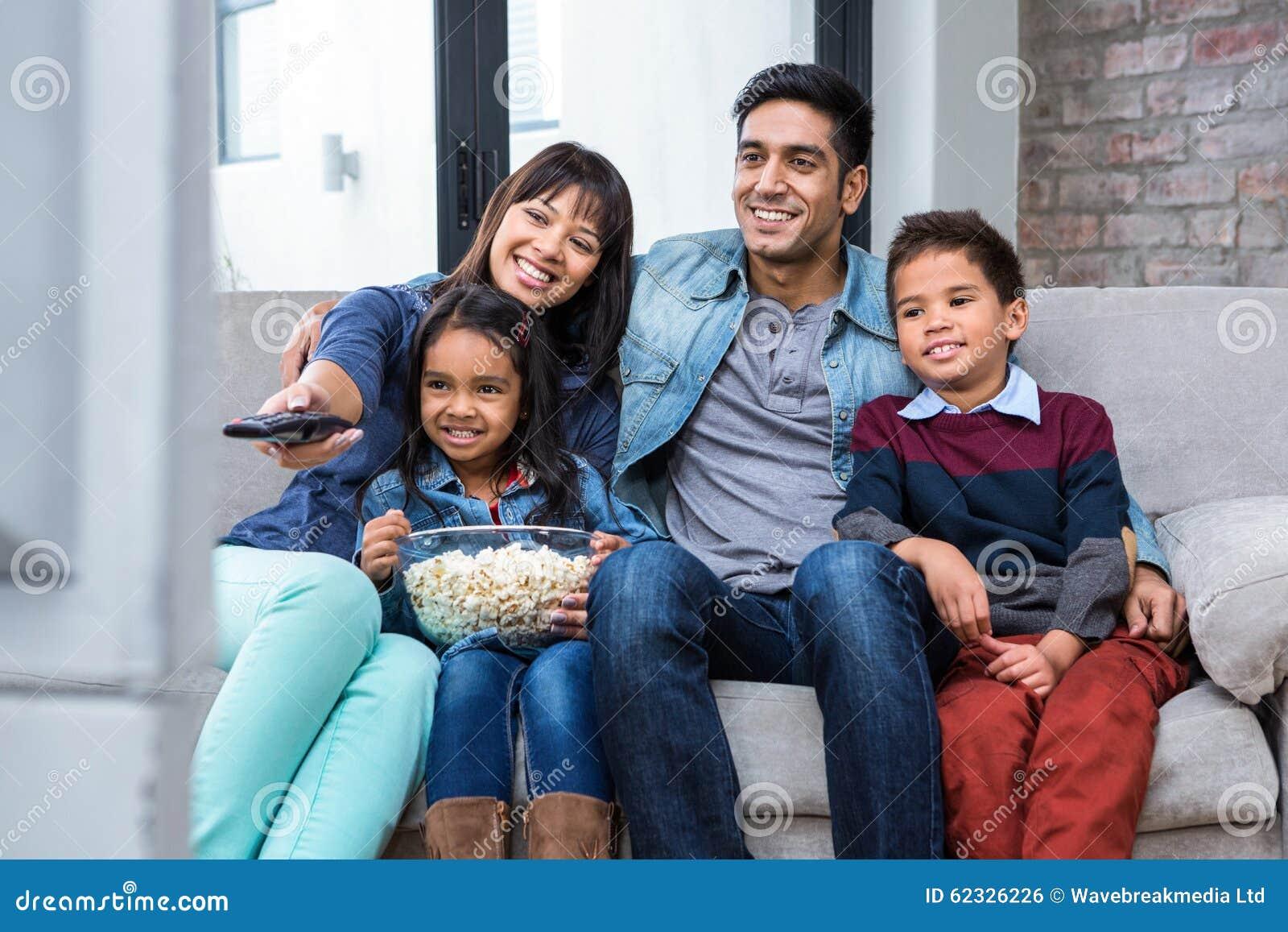 Família nova feliz que come a pipoca ao olhar a tevê