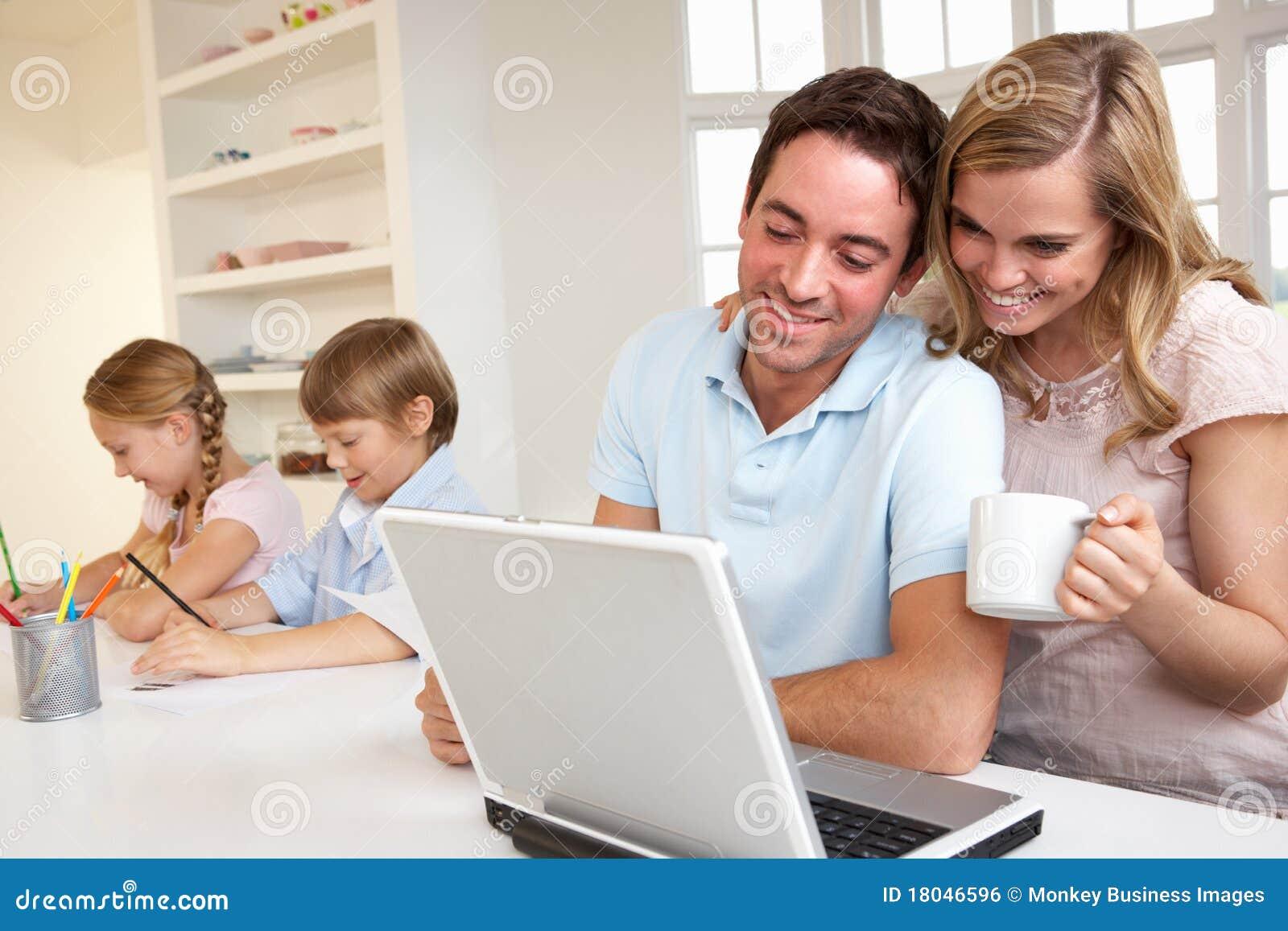 Família nova feliz que olha e que lê um portátil