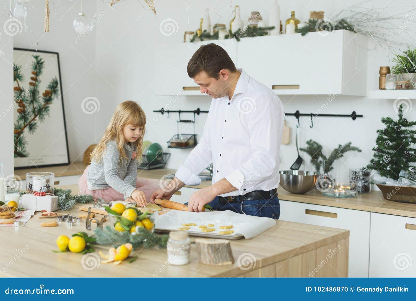 Família nova que faz cookies em casa conceito do alimento, da família, do Natal, do hapiness e dos povos - família de sorriso que