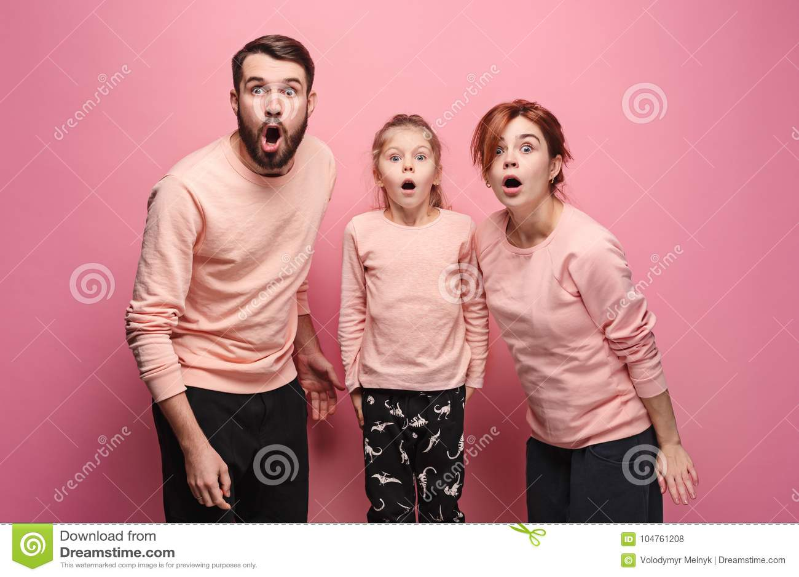 Família nova surpreendida que olha a câmera no rosa