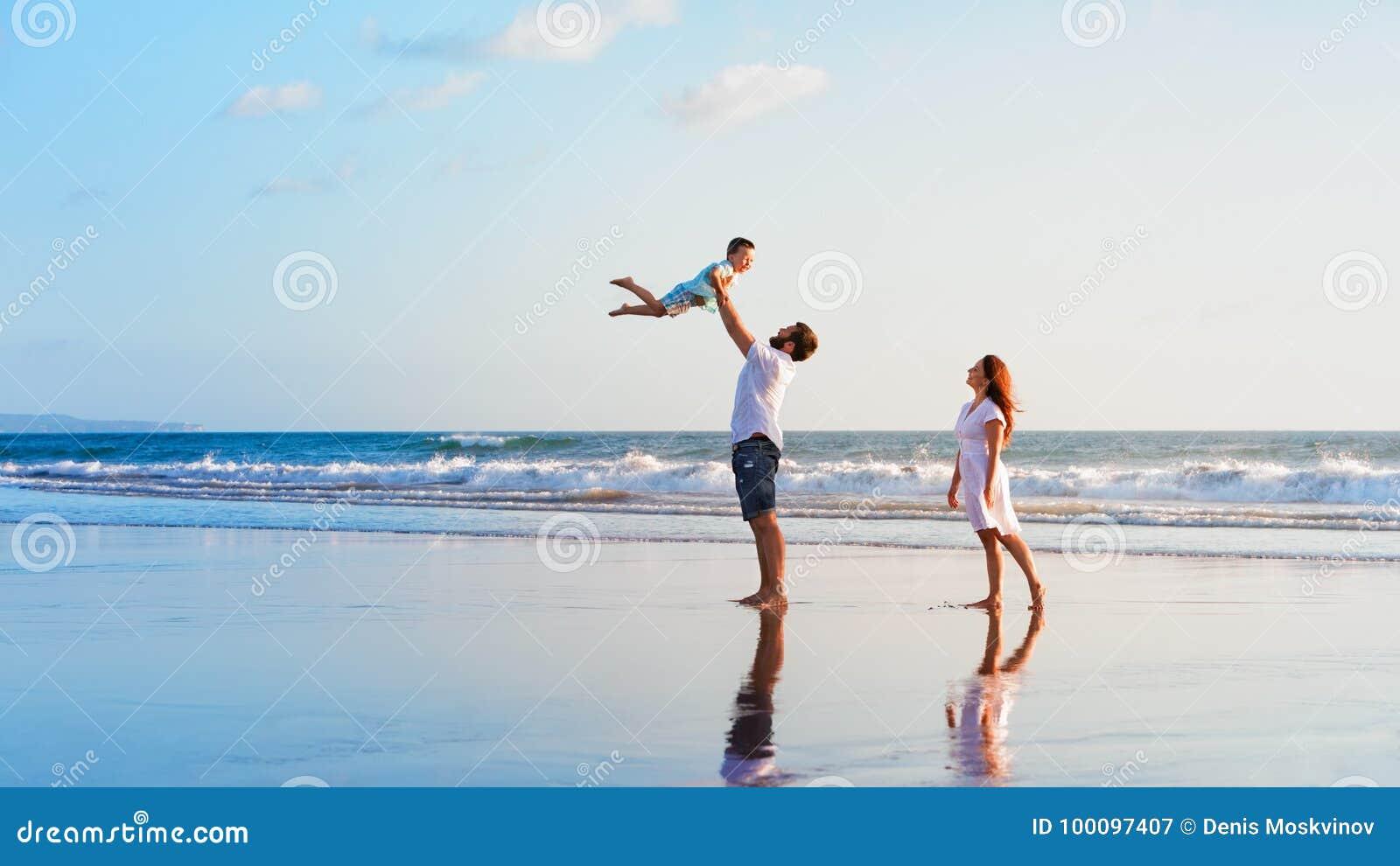 Família - pai, mãe, caminhada do bebê na praia do por do sol