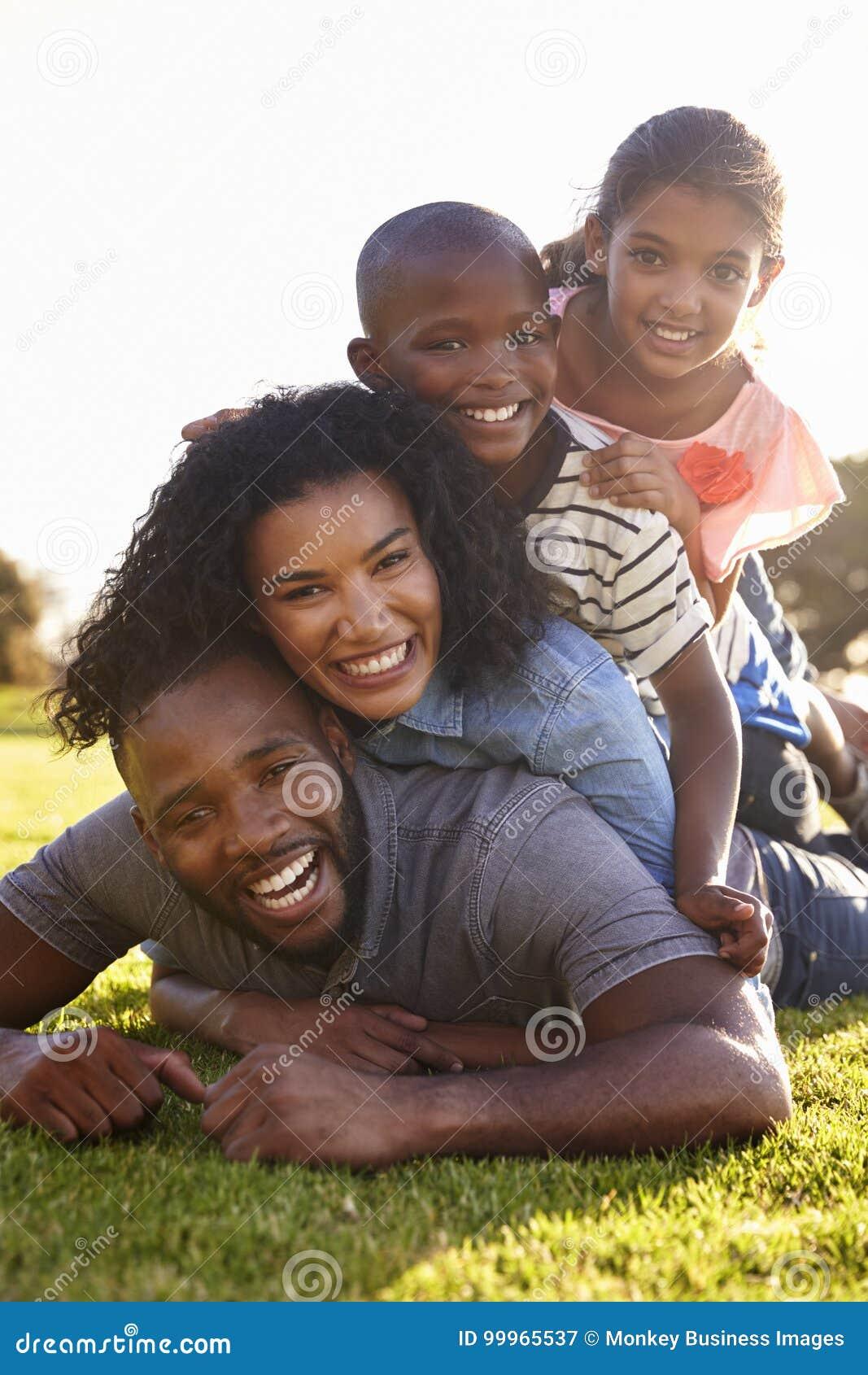 Família preta feliz que encontra-se em uma pilha na grama fora