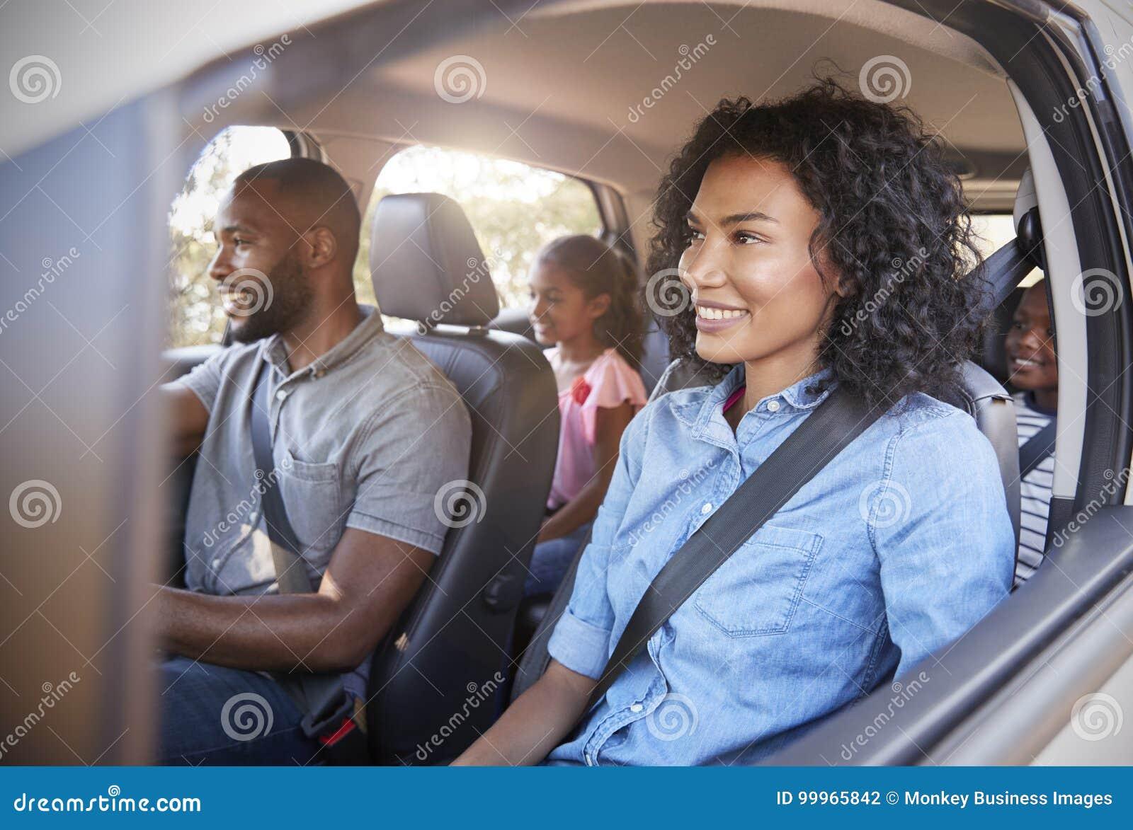 Família preta nova com crianças em um carro que vai na viagem por estrada