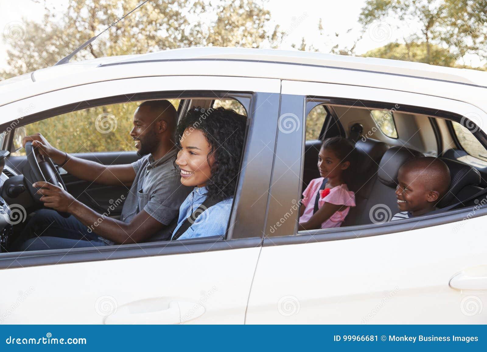 Família preta nova em um sorriso do carro na viagem por estrada