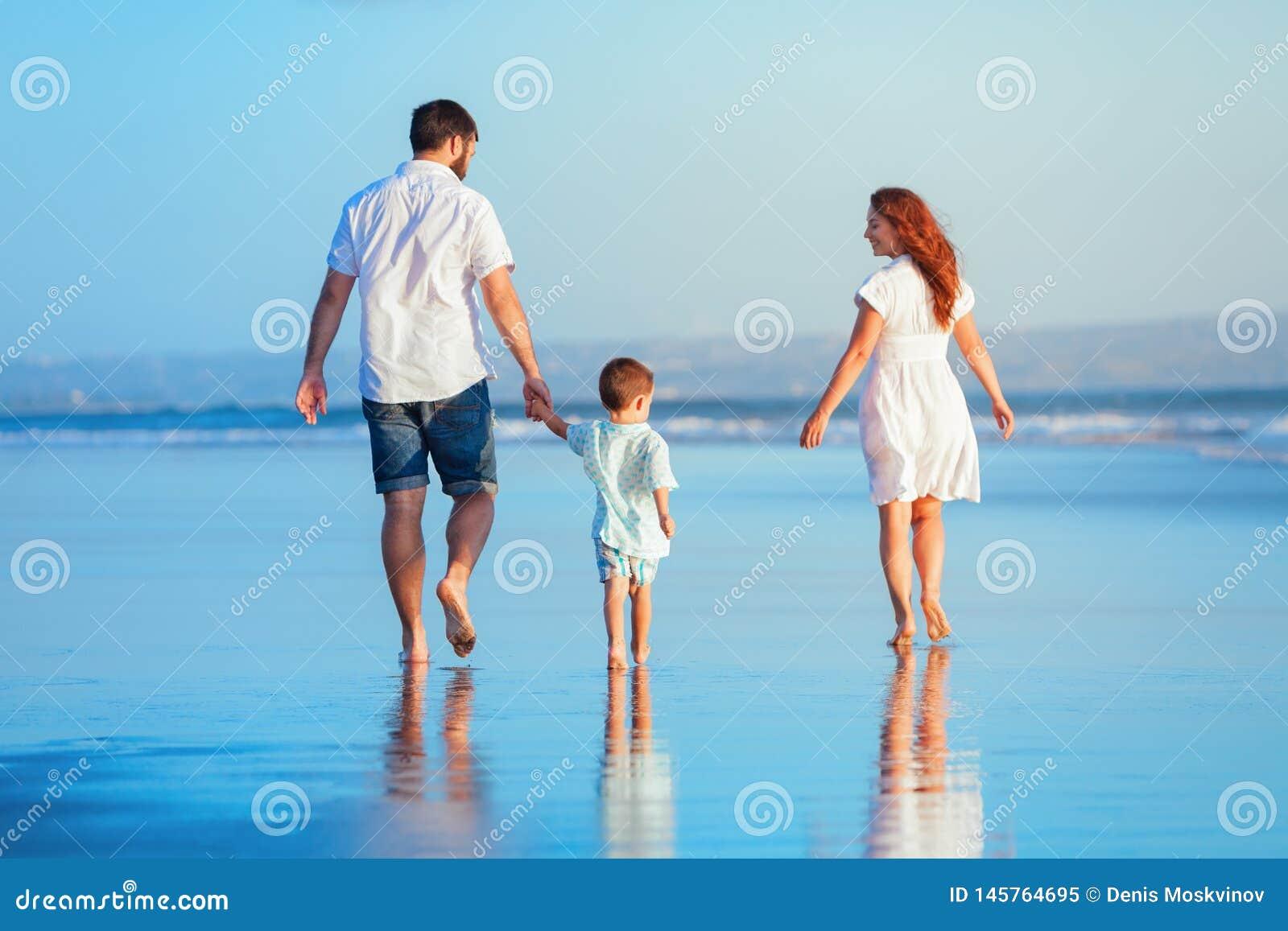 Família que anda pela praia do por do sol