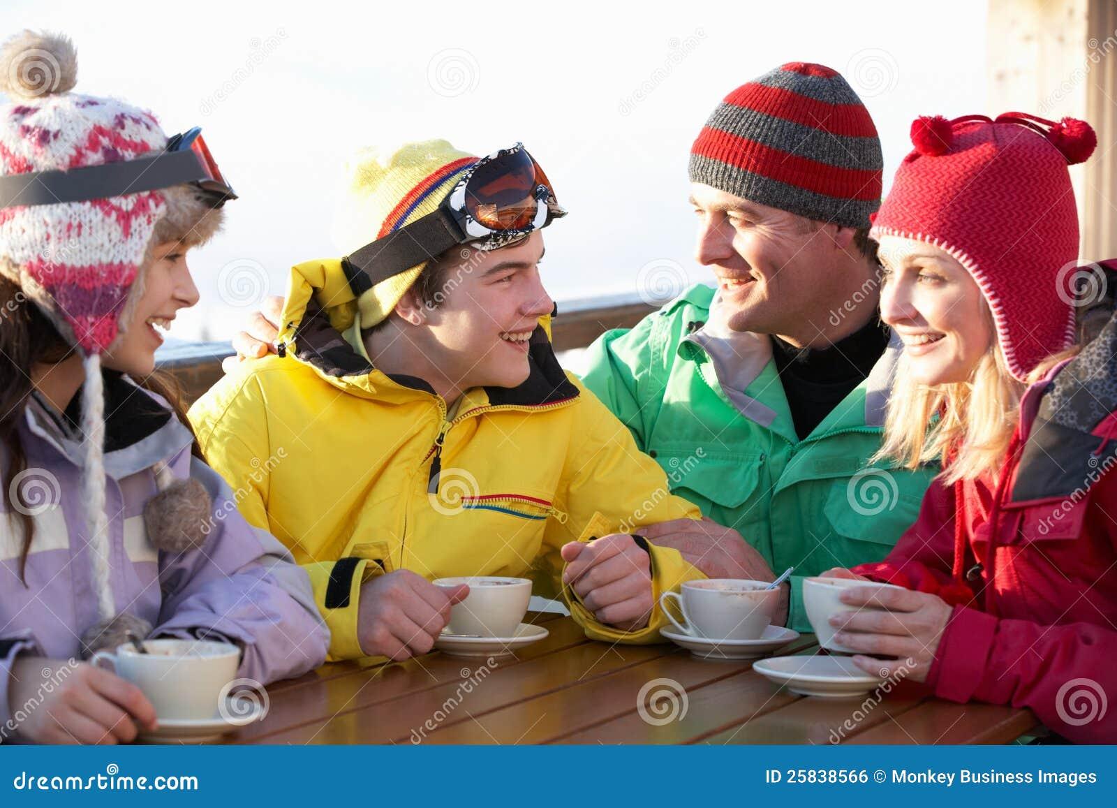Família que aprecia a bebida quente no café na estância de esqui