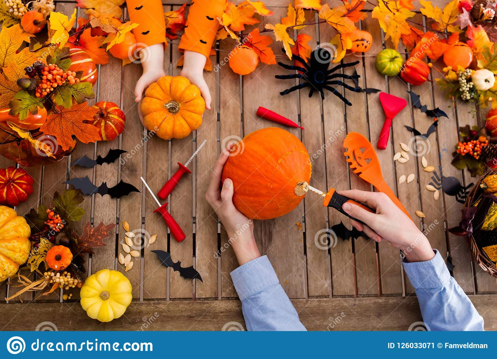 Família que cinzela a abóbora Truque ou deleite de Halloween