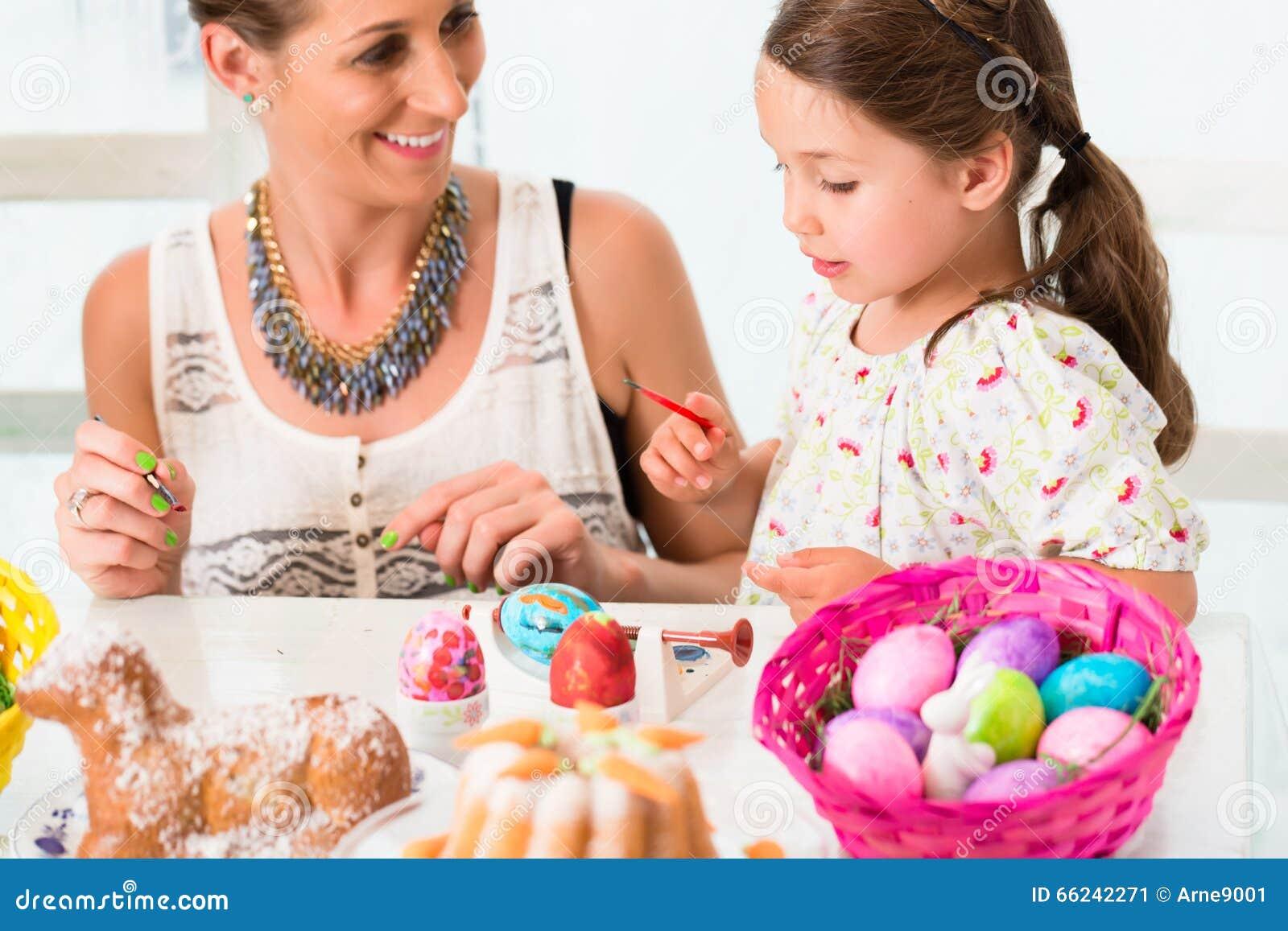 Família que come ovos da páscoa da coloração do divertimento