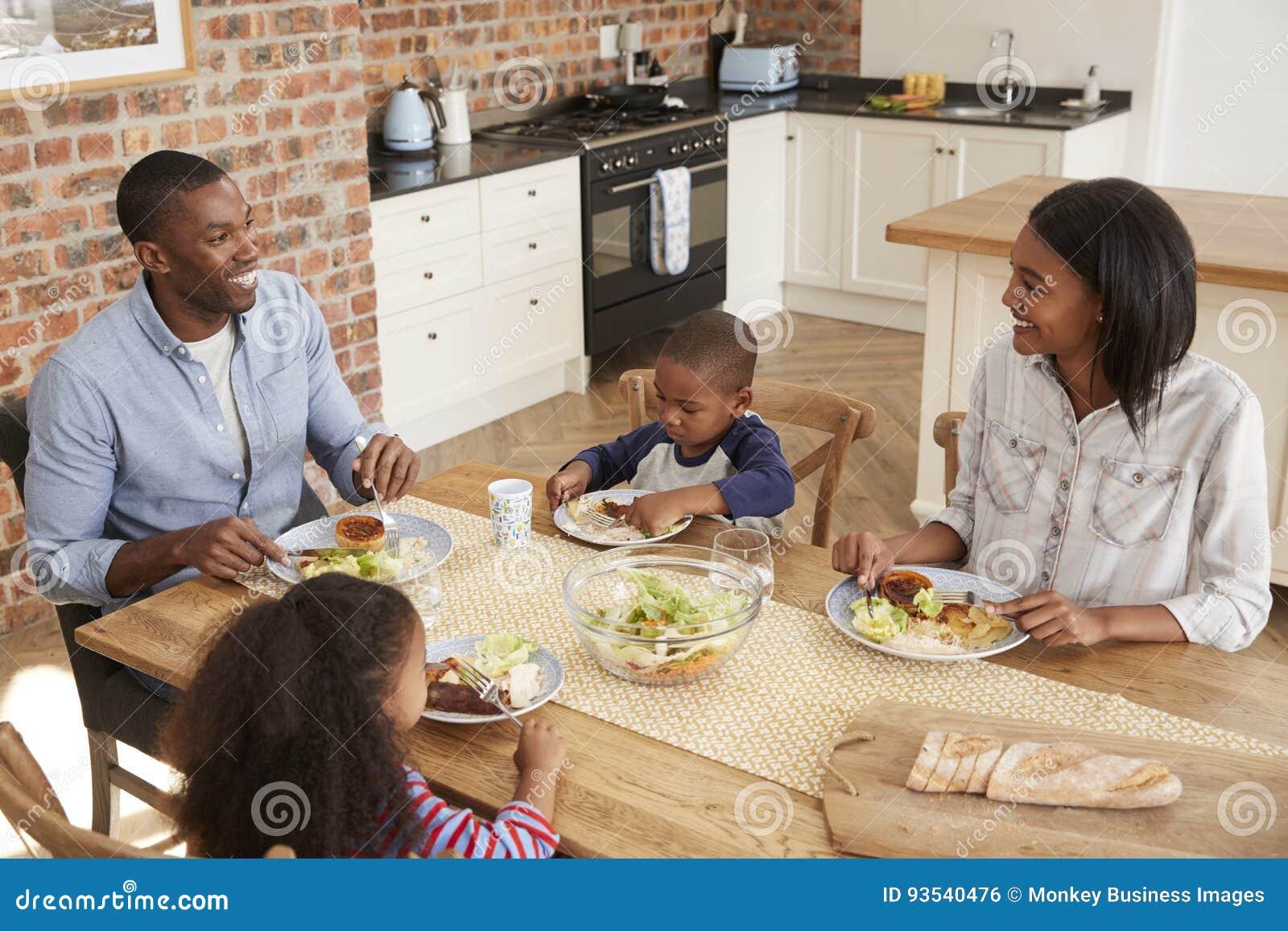 Família que come a refeição na cozinha de plano aberto junto