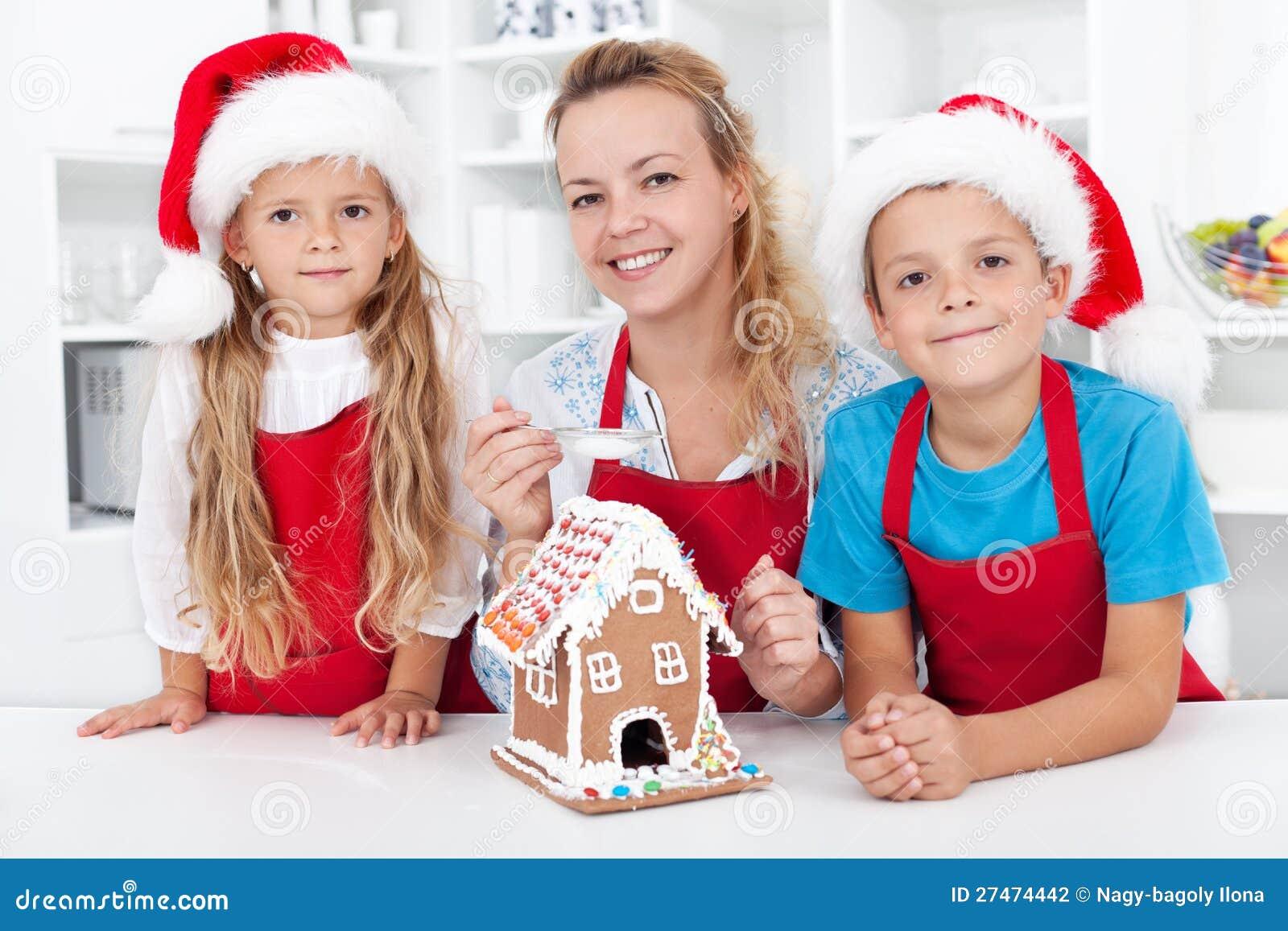 Família que faz uma casa do bolinho do pão-de-espécie